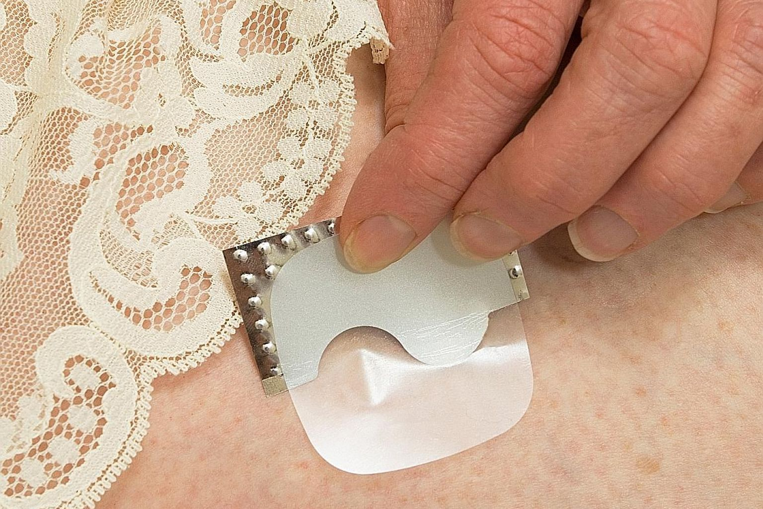 An HRT patch being applied. Hormone replacement therapy can help with hot flushes and sleep disturbance, and it also keeps the bones strong.