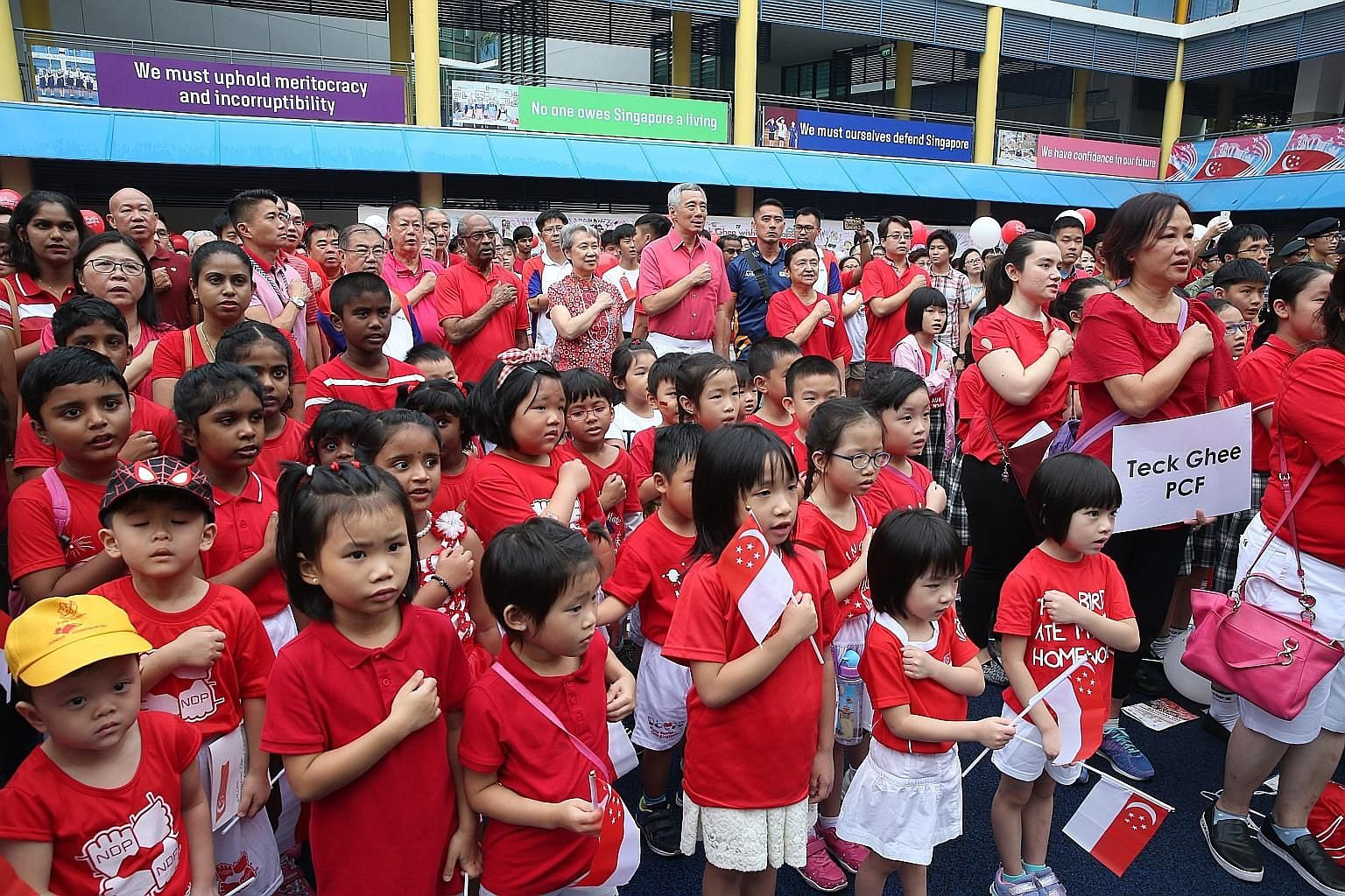 Prime Minister Lee Hsien Loong and Mrs Lee reciting the Pledge with residents, grassroots leaders and children at the Teck Ghee National Day Observance Ceremony yesterday.