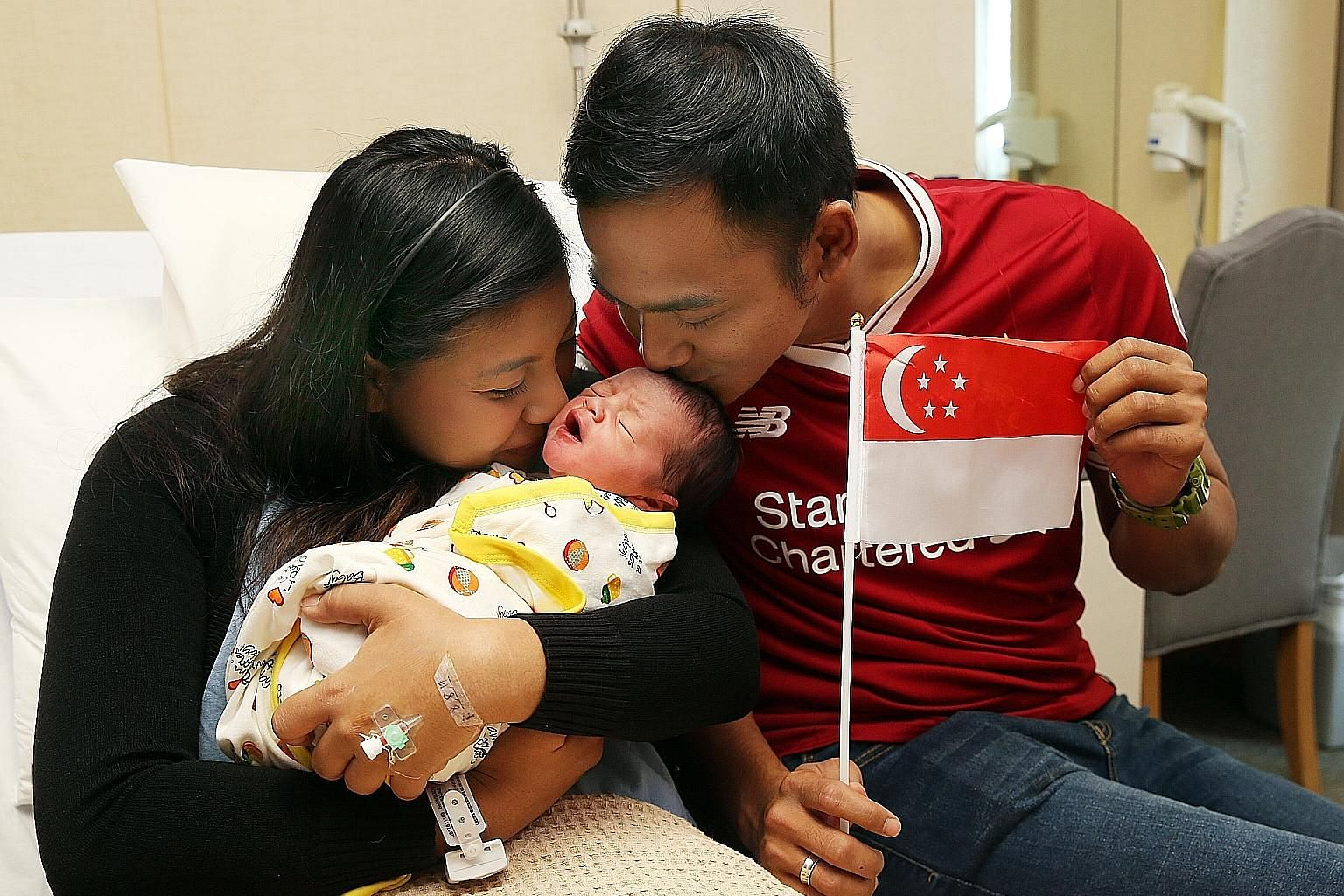 Above: Ms Soh Bei En with her newborn son Matheus Tan Pin Xu at Mount Alvernia Hospital yesterday. The baby boy is the first child of Ms Soh and her husband Tan Shi Chang, and was six days overdue. Left: Madam Rabitah Razali, Mr Eddy Kurniawan and th