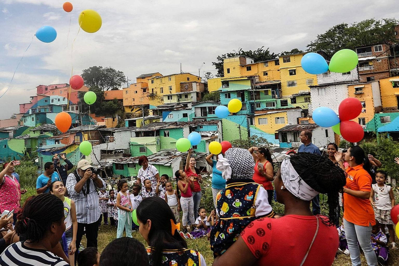 Residents of El Pesebre, a shanty town on the outskirts of Medellin in Colombia, celebrating French street artist Tarik Bouanani's art project on Wednesday. With the help of residents, Bouanani turned the 230 brick houses in the town into a giant mur