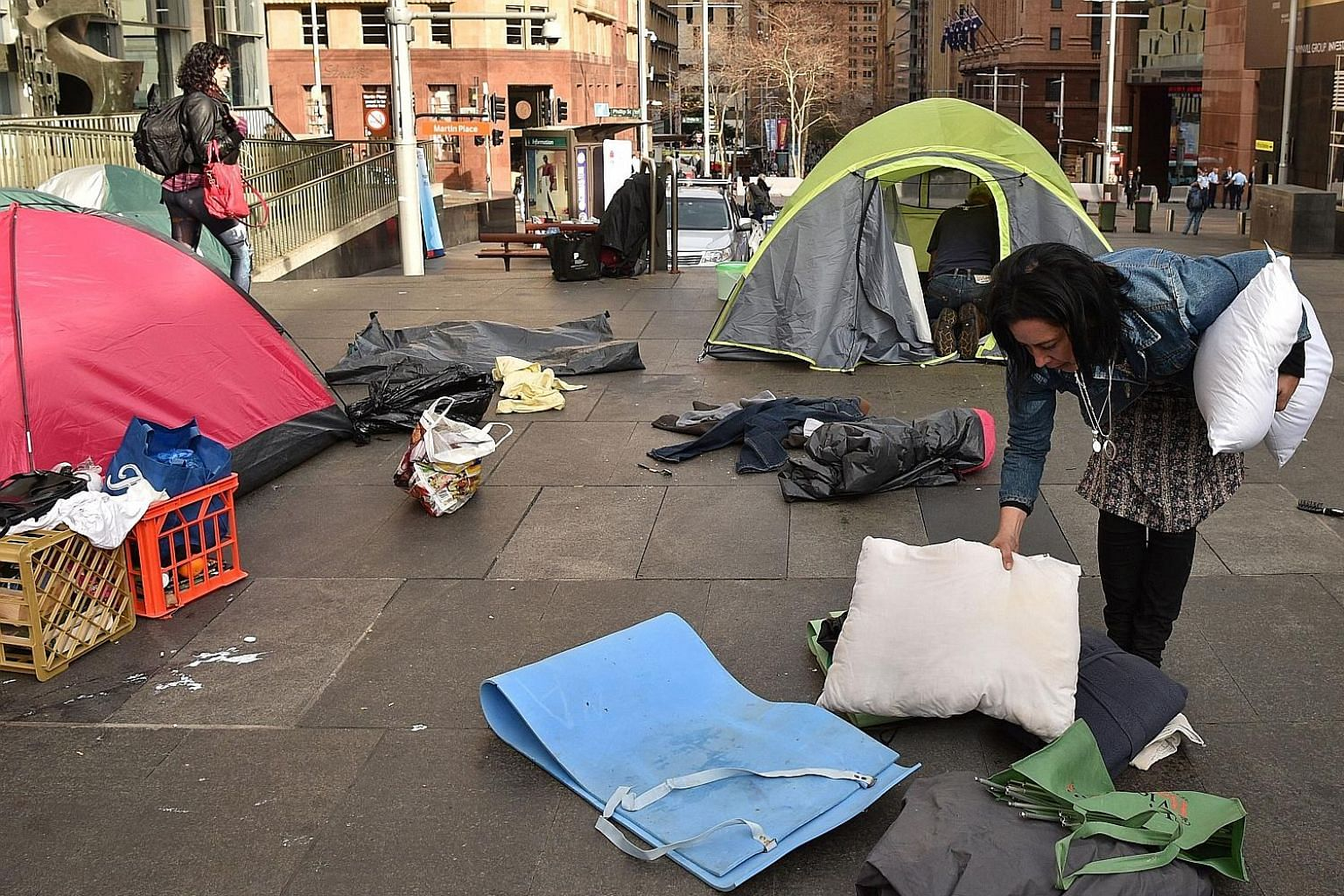 """A homeless woman packing up her belongings in Martin Place, which had become known as """"tent city"""", in the central business district of Sydney yesterday. The camp had become the most visible symbol of the lack of low-cost accommodation in Sydney."""