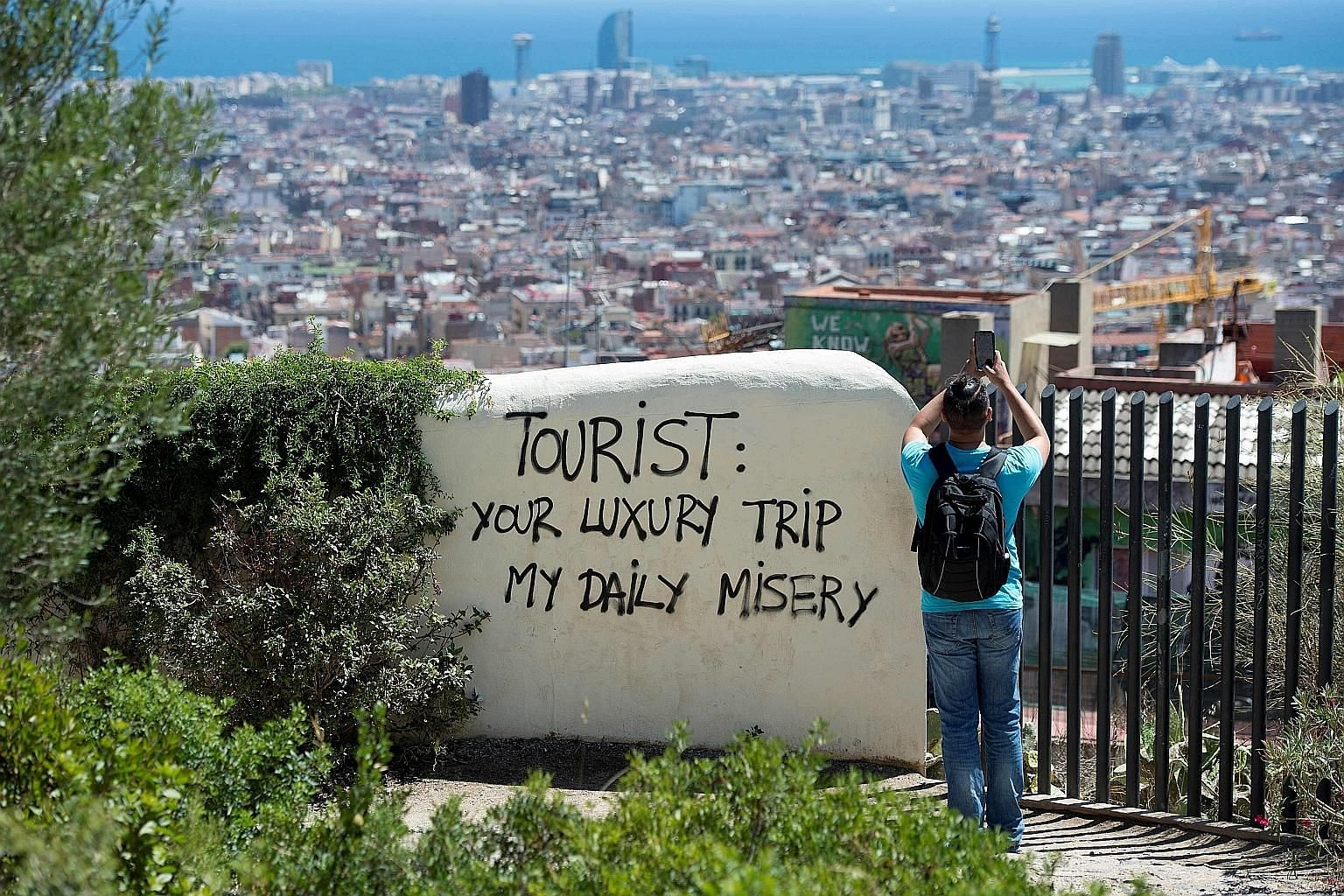 """Ignoring the """"less than friendly"""" graffiti, a tourist is focused on snapping a photo of Barcelona on Thursday."""