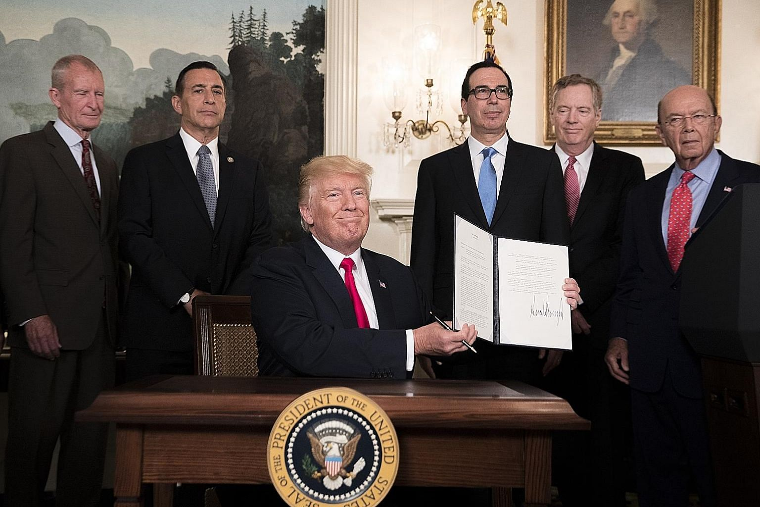 US President Donald Trump in the Diplomatic Reception Room of the White House on Monday with a signed memorandum calling for a trade investigation of China. With him are his inner circle who deal with trade issues, including Commerce Secretary Wilbur