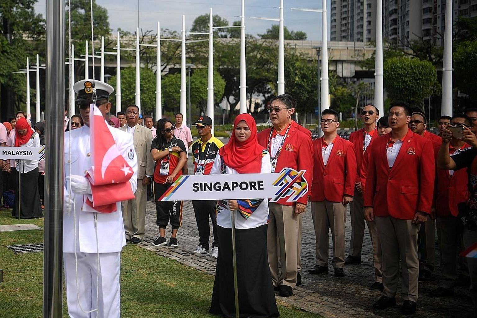 Members of Team Singapore, including chef de mission Milan Kwee (in sunglasses behind placard) sing the national anthem during yesterday's SEA Games welcome ceremony. The flag-raising for the 11 participating nations was held at the Bukit Jalil Natio