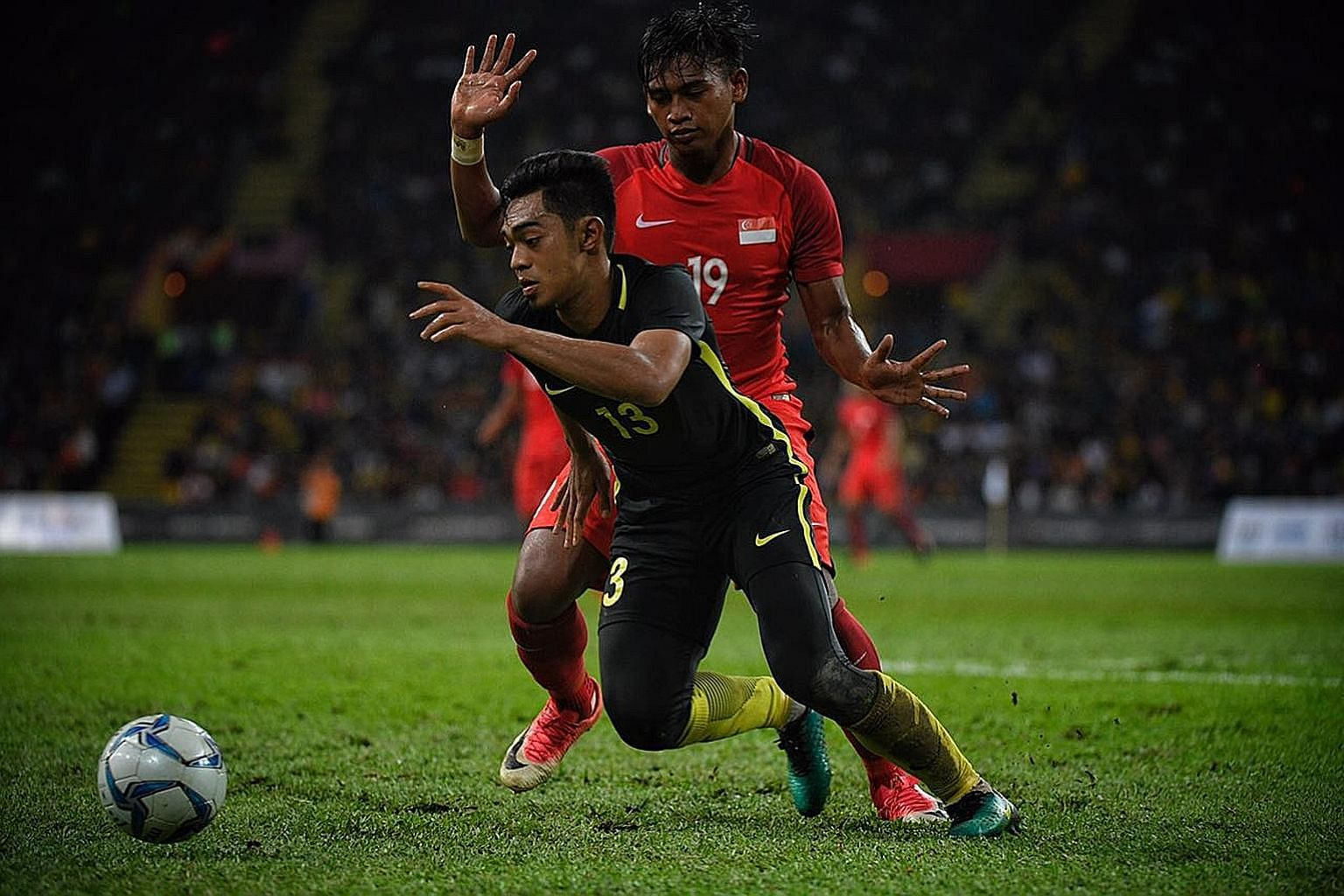 Singapore's scorer Amiruldin Asraf Nodin battling for the ball against Ariff Farhan Isa of Malaysia in their match at Shah Alam Stadium. The Young Lions must beat both Laos and Brunei by big margins and hope either the hosts or Myanmar lose both thei