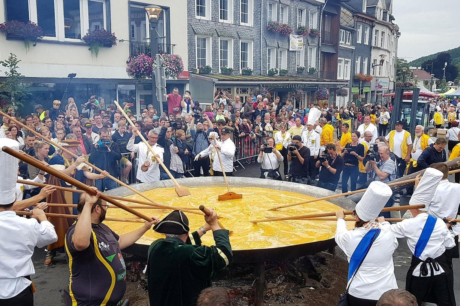 Members of The World Fraternity of Knights of the Giant Omelette, created in 1973, honouring their 22-year-old tradition of making a giant omelette despite an egg contamination scare. They cooked 10,000 eggs in a 4m-wide pan over an open fire as musi