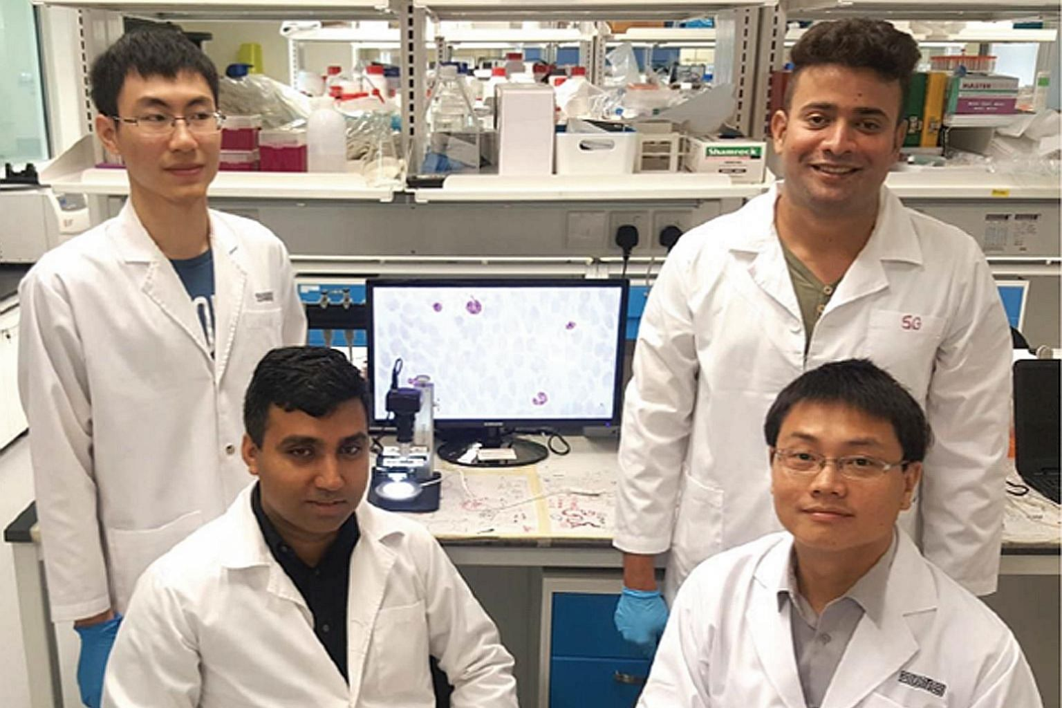 The new cytometer (left) that employs image processing and machine-learning algorithms to count infected blood cells digitally is developed by an SUTD team comprising (anticlockwise from bottom right) Dr Ye Ai, Dr Rajesh Chandramohanadas and graduate