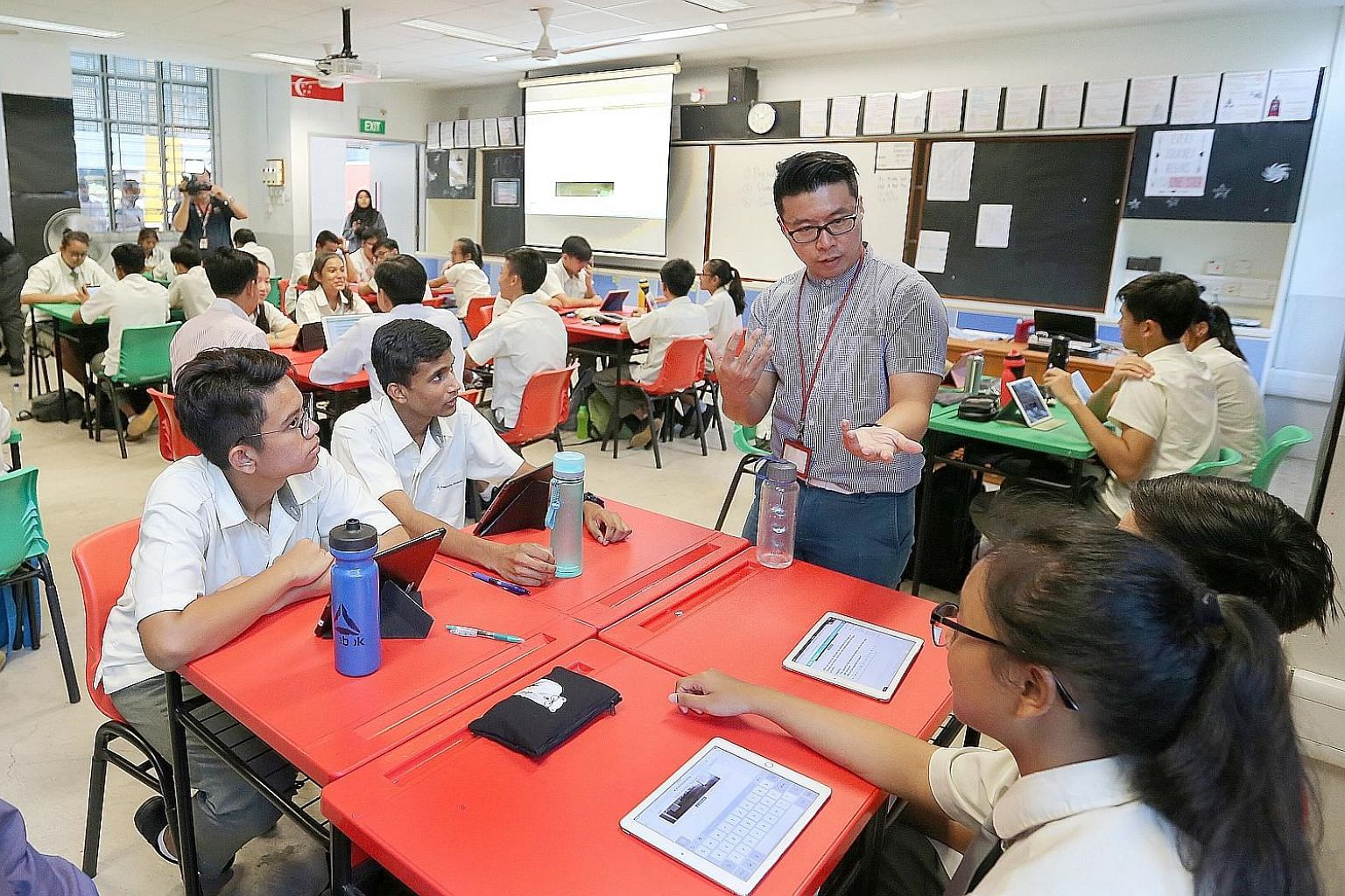 Social studies teacher Tay Peiyong with his students from Admiralty Secondary School on Wednesday. The school is one of 62 where the Singapore Student Learning Space is being piloted.