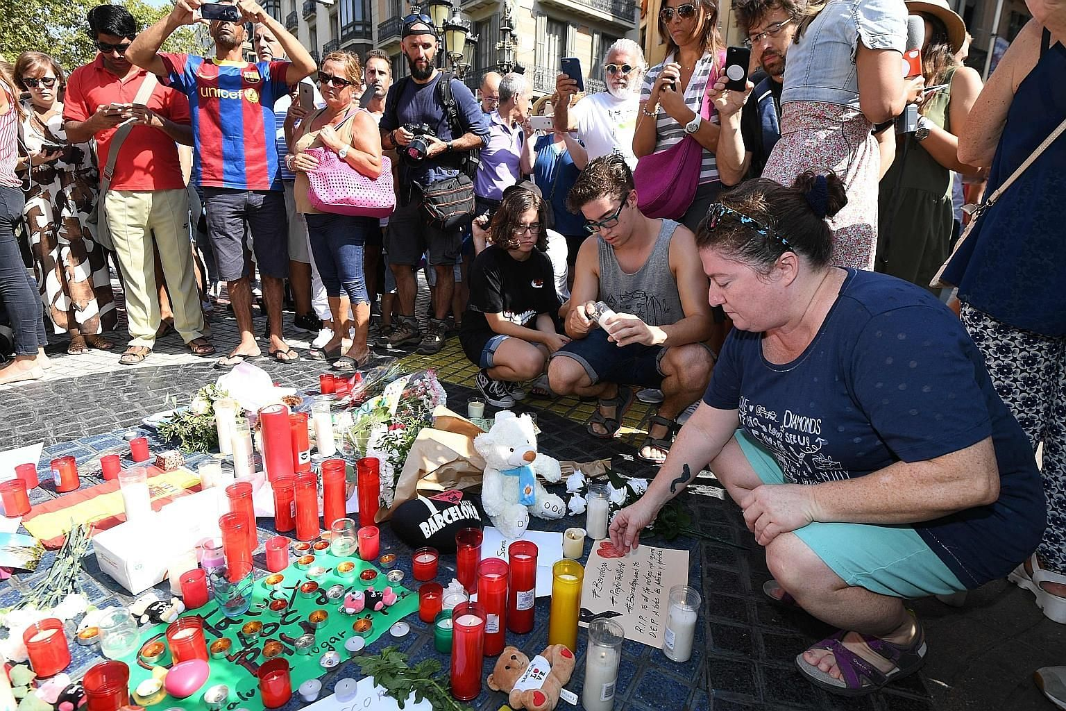 People paying their respects to the victims of the van attack at a makeshift memorial set up on the Las Ramblas promenade in Barcelona yesterday. The attack killed at least 13 people and injured more than 100 others.
