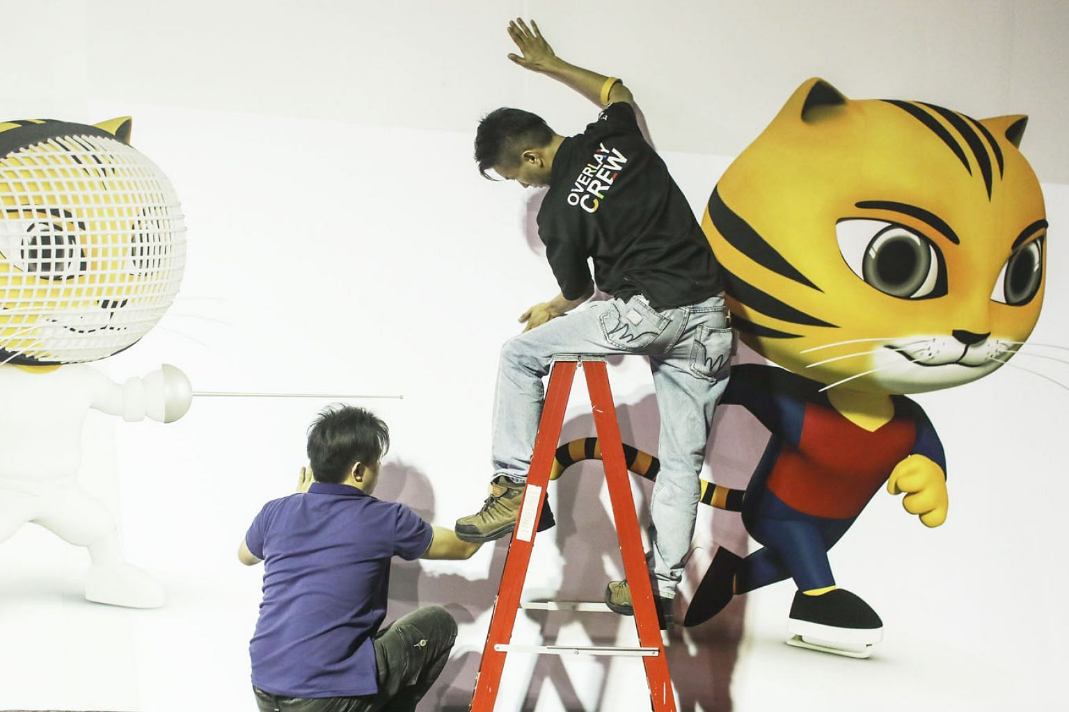 Workers putting up a SEA Games billboard in the main media centre in Kuala Lumpur last week, before the start of the sporting event today. The host nation gets to decide what sports to drop and include and, in recent years, this leeway has become a t