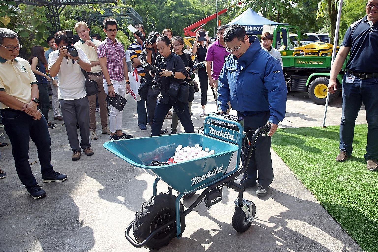 Mr Desmond Lee trying his hand at a battery-powered wheelbarrow while wearing a cordless fan jacket at the Landscape Industry Fair in HortPark yesterday. Both items are equipment used in landscaping work.