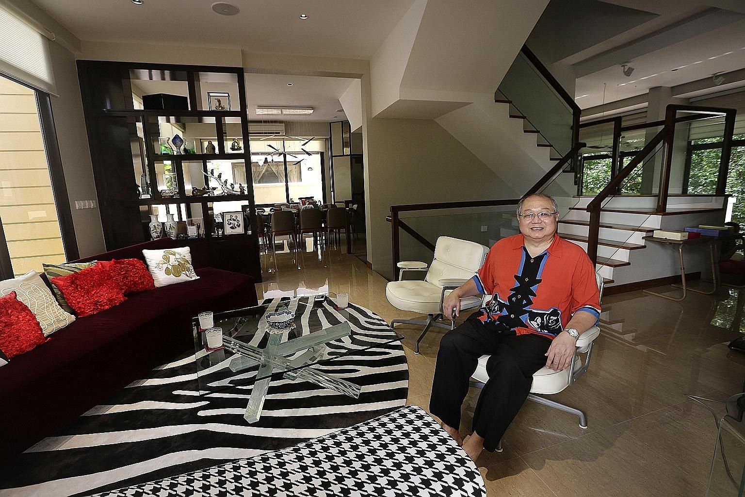 Former group chief financial officer of Neptune Orient Lines Lim How Teck in his living room, where he enjoys entertaining guests. The wall dividing the two houses was removed to open into another dining area. He moved into the cluster housing develo