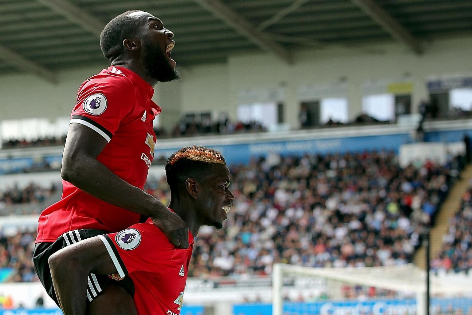 Manchester United's Paul Pogba celebrates his goal with Romelu Lukaku (top) after making it 3-0 against Swansea at the Liberty Stadium. Lukaku was also on the scoresheet, with United winning 4-0.