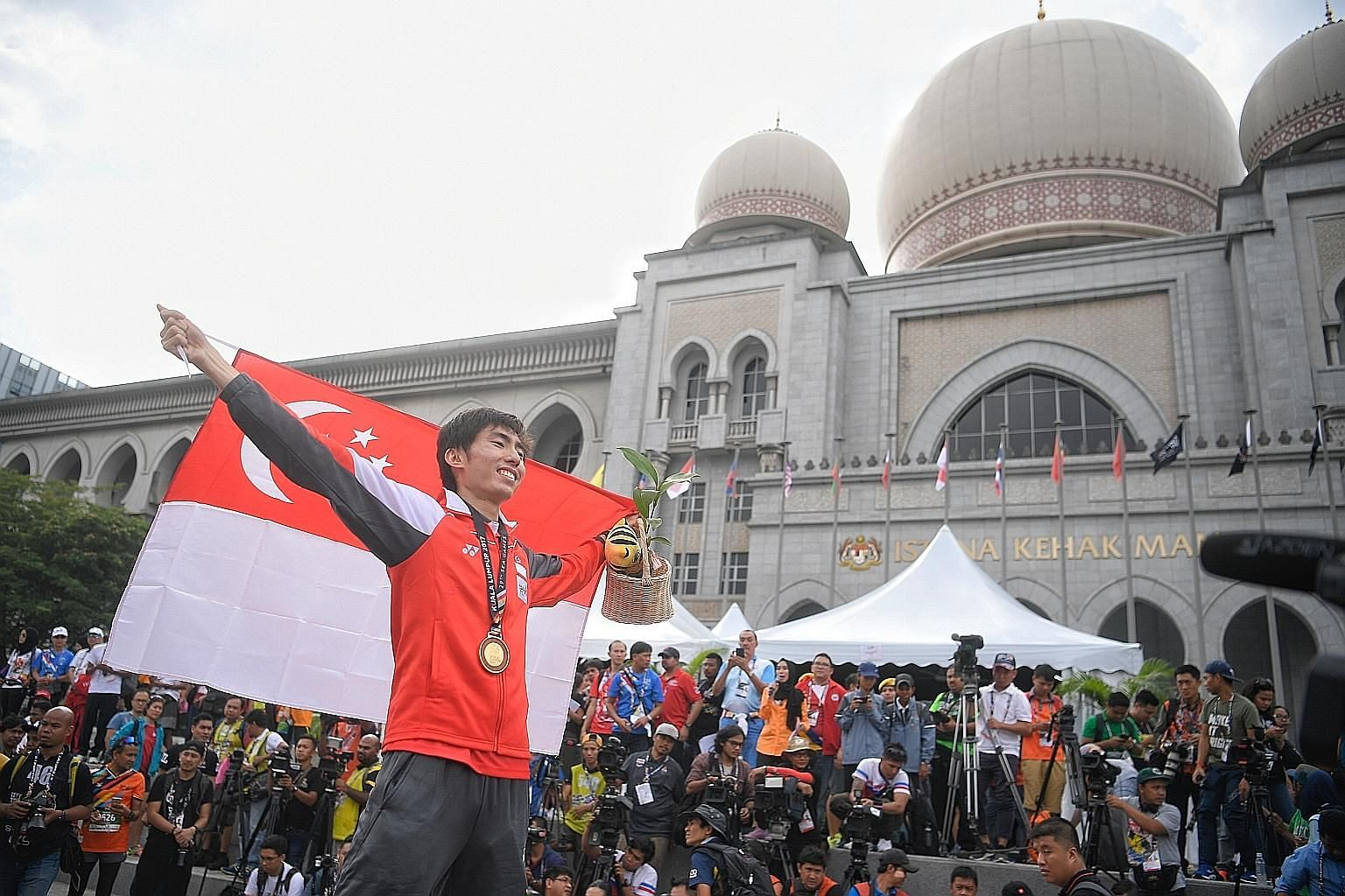 Singapore marathoner Soh Rui Yong celebrating his victory on the podium in front of the Istana Kehakiman, in Putrajaya, yesterday. The Republic's women's water polo team also picked up a silver medal.