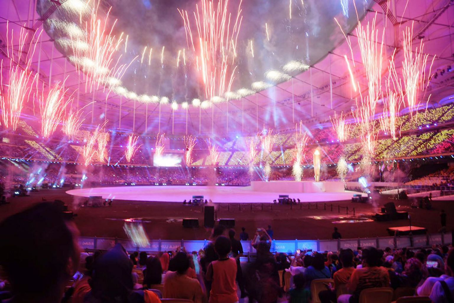 Fireworks; the performers including wushu exponents and traditional dancers; and the Singapore contingent, led by shooter Jasmine Ser, walking out during the athletes' parade at the Bukit Jalil National Stadium yesterday.
