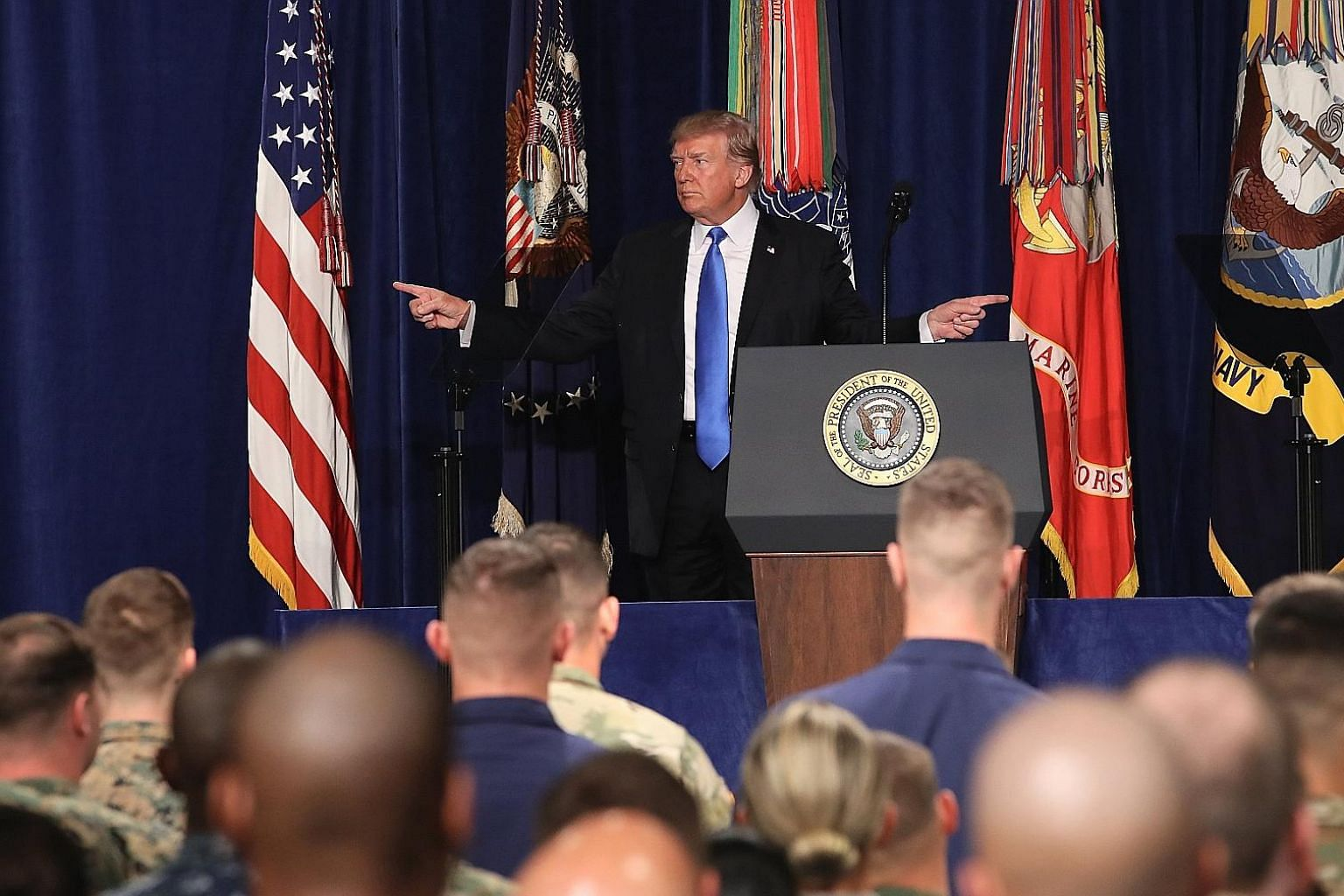 Left: US President Donald Trump before delivering remarks on his country's military involvement in Afghanistan at the Fort Myer base, in Virginia, on Monday. The US is expected to send about 4,000 troops to join the roughly 8,400 in Afghanistan to be