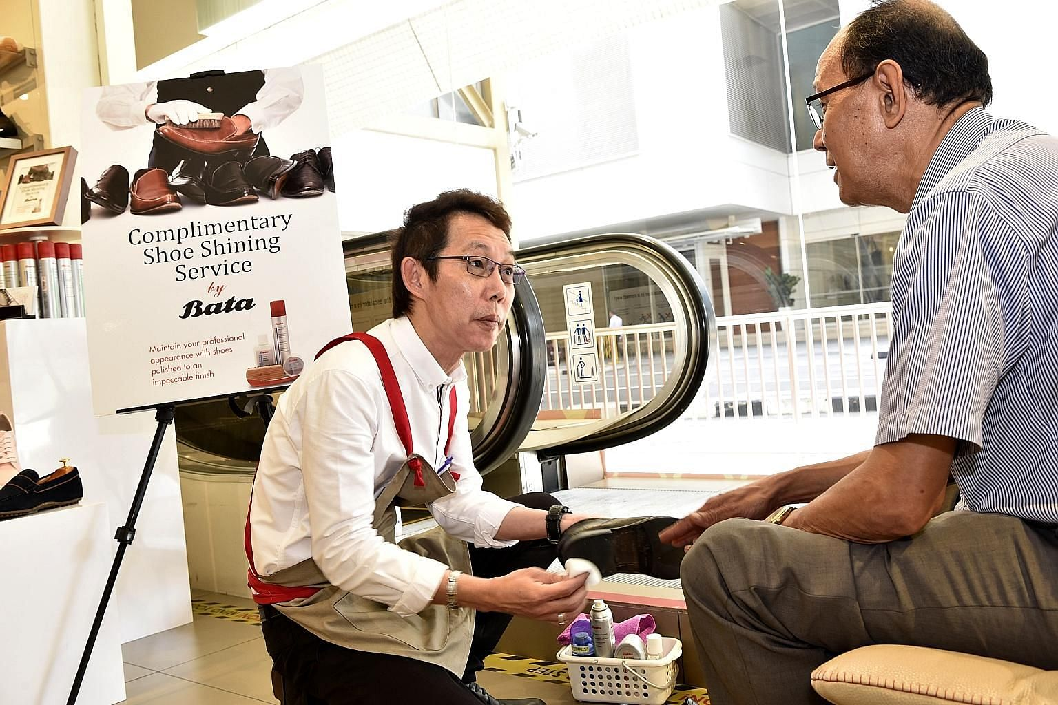Store manager Desmond Wee polishes Mr Zulkipli Lahom's shoes at Bata's Peninsula Plaza flagship store yesterday.