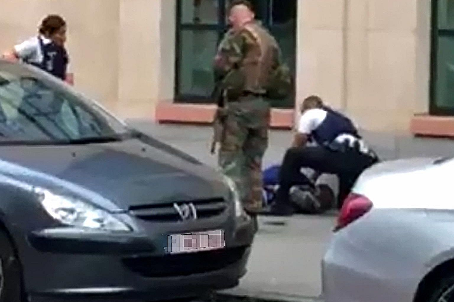 The man who allegedly wounded a soldier with a knife on Friday night in central Brussels lying on the ground after being shot. Police also found a replica gun and two copies of the Quran on him.