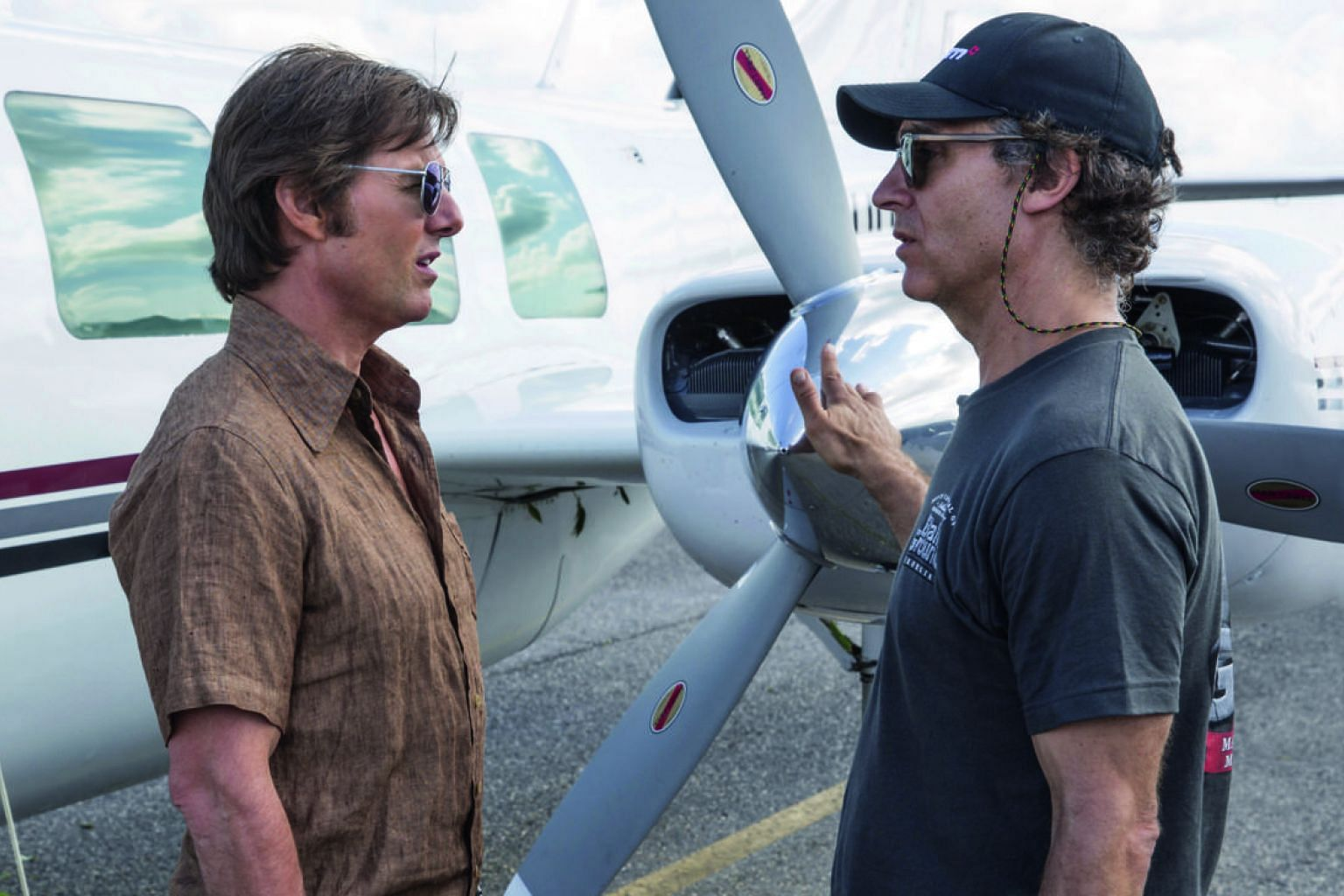 Director Doug Liman with Tom Cruise (far left) on the set of American Made.