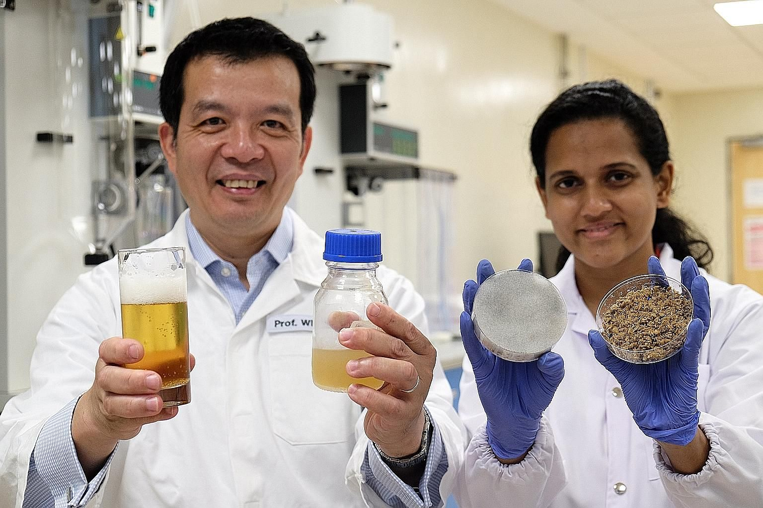 Prof William Chen and PhD student Sachindra Cooray holding (from right) the brewer's spent beer grains, the fermented spent beer grains, the liquid nutrient used to grow yeast, and beer.