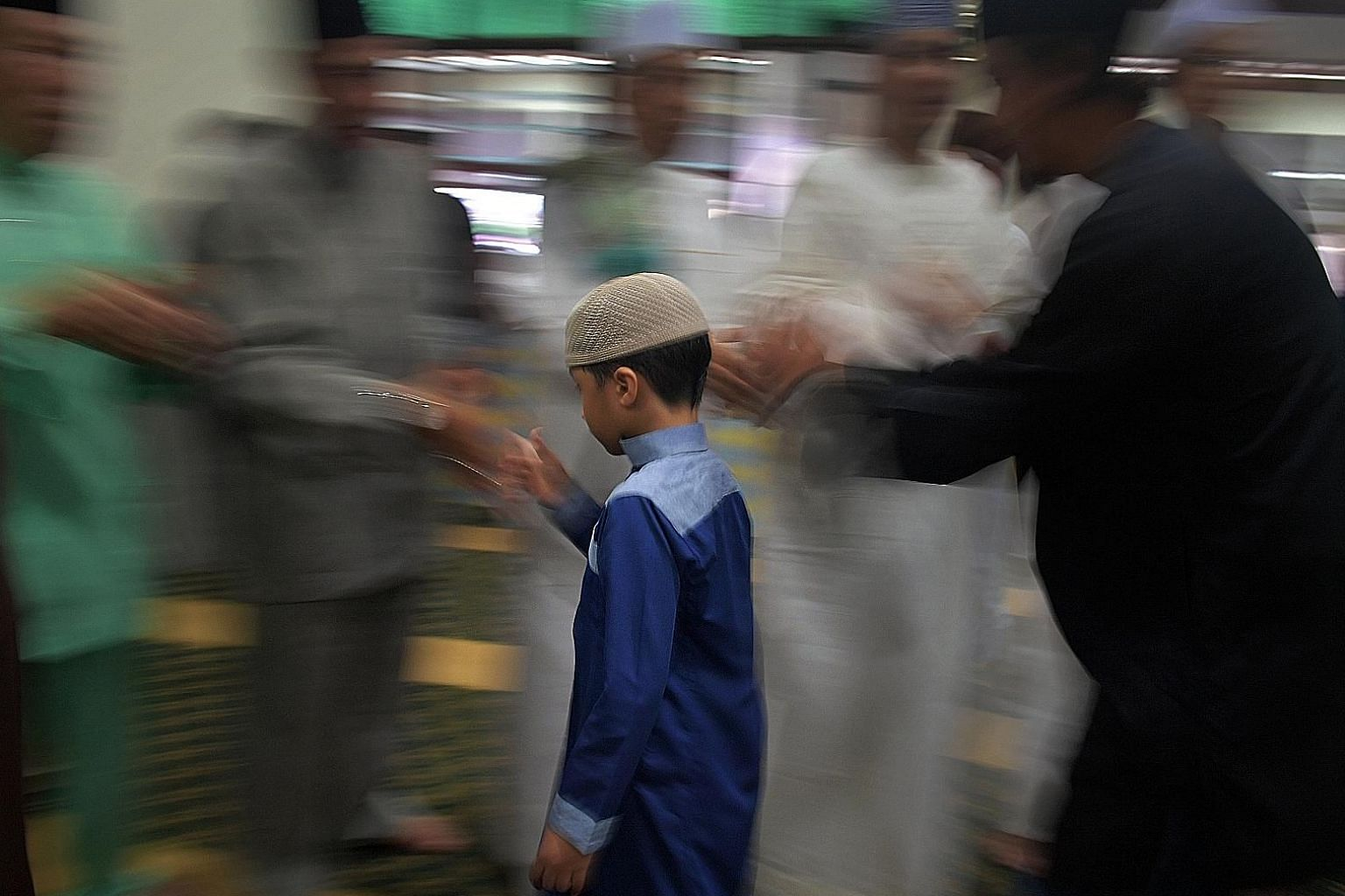 A boy paying his respects to his elders after prayers at the mosque yesterday. Some 850 congregants gathered there to mark the end of the annual haj pilgrimage.