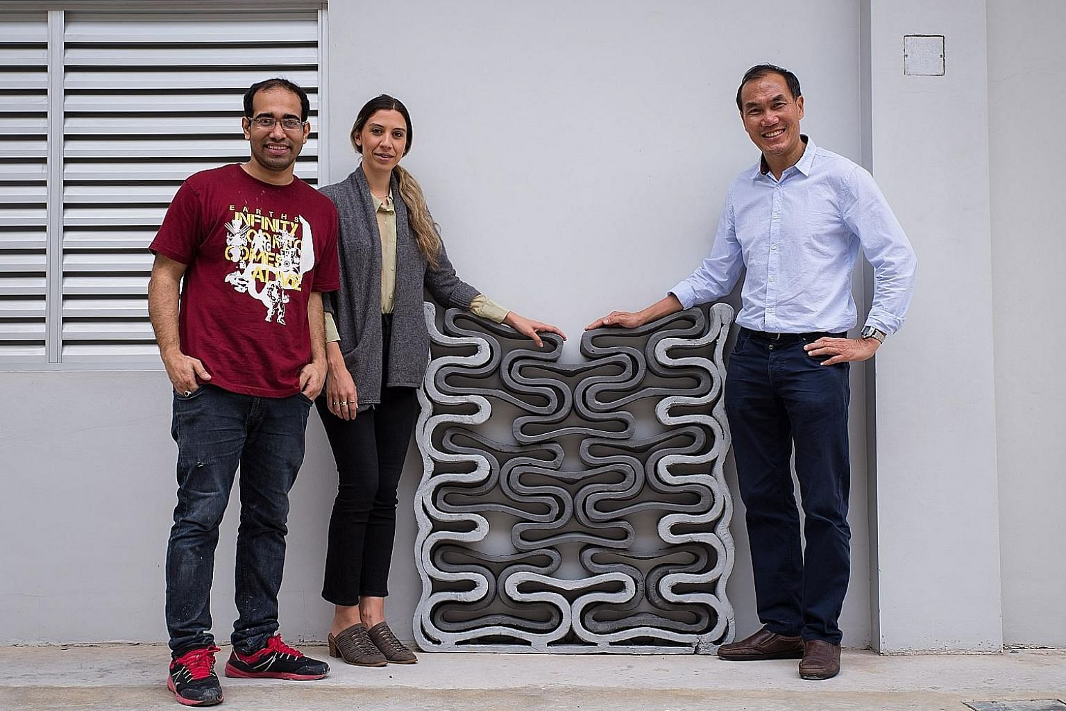 Left: A small-scale version of a squash court whose walls are 3D-printed using a material comprising fly ash, a by-product from coal burning. Above (from left): NTU PhD student Panda Biranchi Narayan, research associate Catherine Soderberg and Associ
