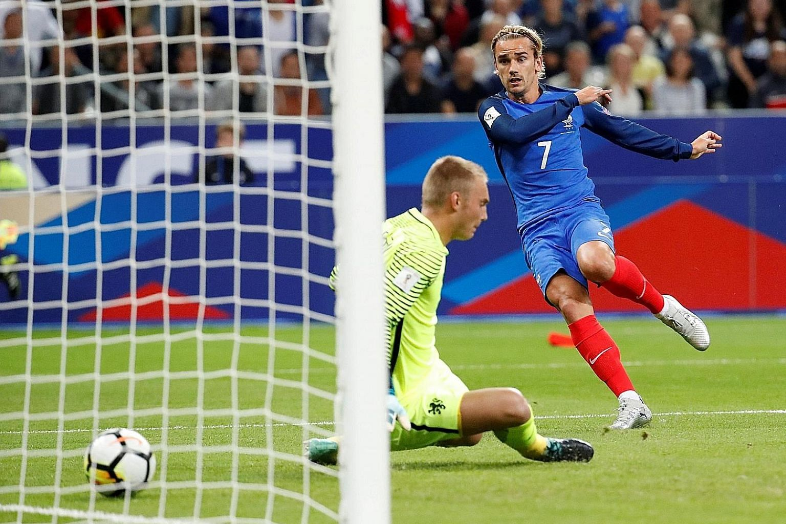 Left: Antoine Griezmann scores France's first goal past Dutch custodian Jasper Cillessen. Below: France midfielder Thomas Lemar celebrating one of his two goals, as his team cemented top spot in their qualifying group with the 4-0 win.