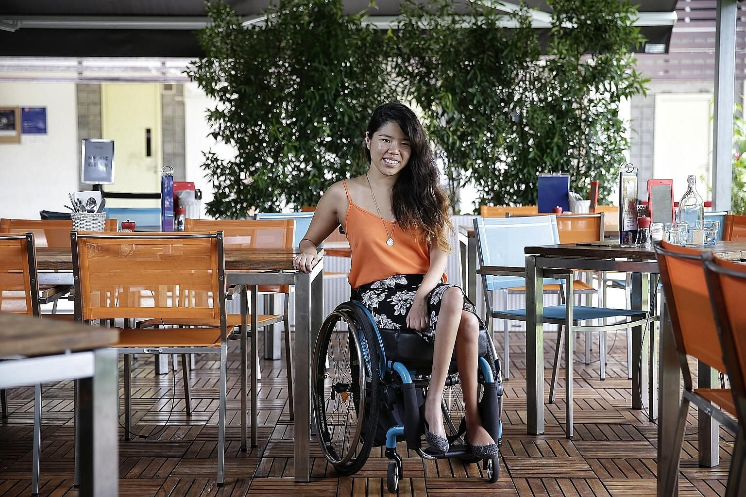 Swimmer Yip Pin Xiu, seen here at Cafe Melba, travels independently, taking taxis or Uber or Grab. She notes that attitudes towards the disabled here have improved in the last few years.