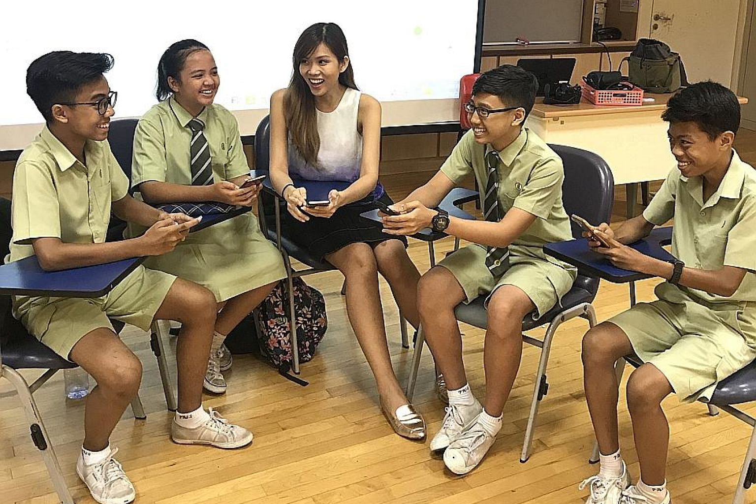 Miss Mavis Ho facilitating a group discussion with her students, using the NewsEd app.
