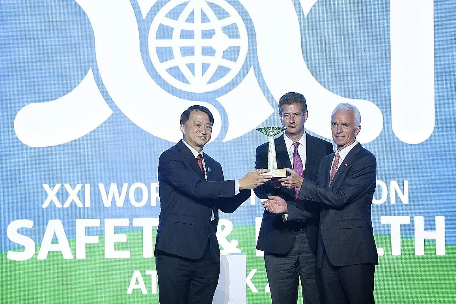 Singapore Commissioner for Workplace Safety and Health Ho Siong Hin (left) presenting a Supertree replica to Canadian Centre for Occupational Health and Safety chief Gareth Jones (centre) and Institute for Work and Health president Cameron Mustard as