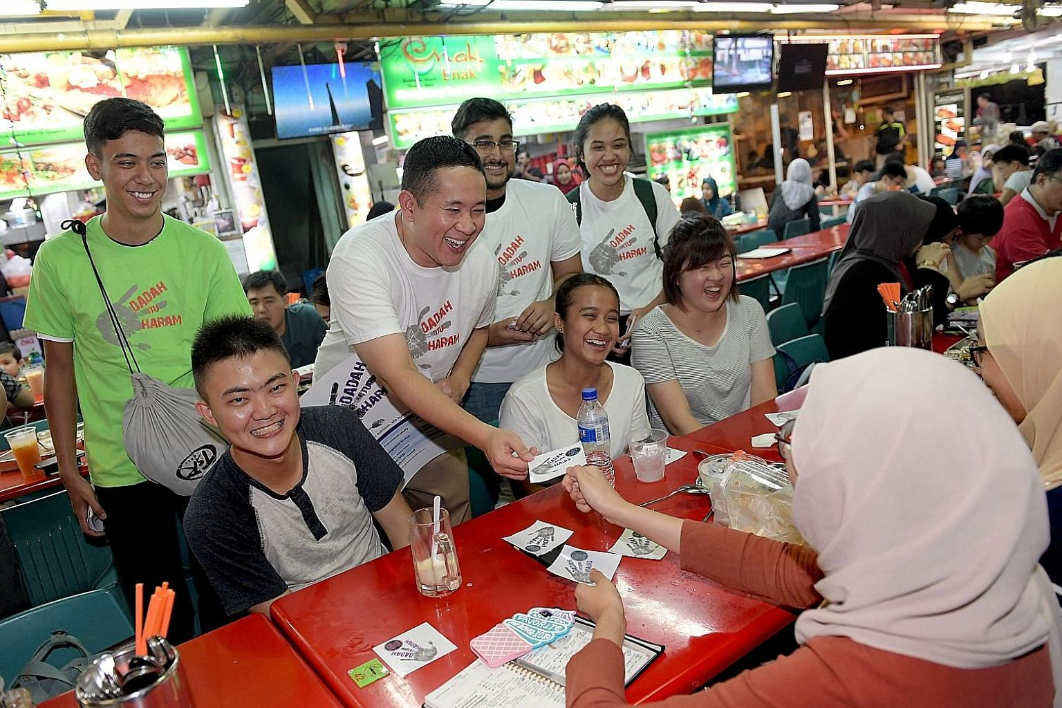 Parliamentary Secretary for Home Affairs Amrin Amin (standing, second from left) and volunteers, including Hairul Marvin (left in green), 17, giving out anti-drug stickers to patrons in Simpang Bedok yesterday.