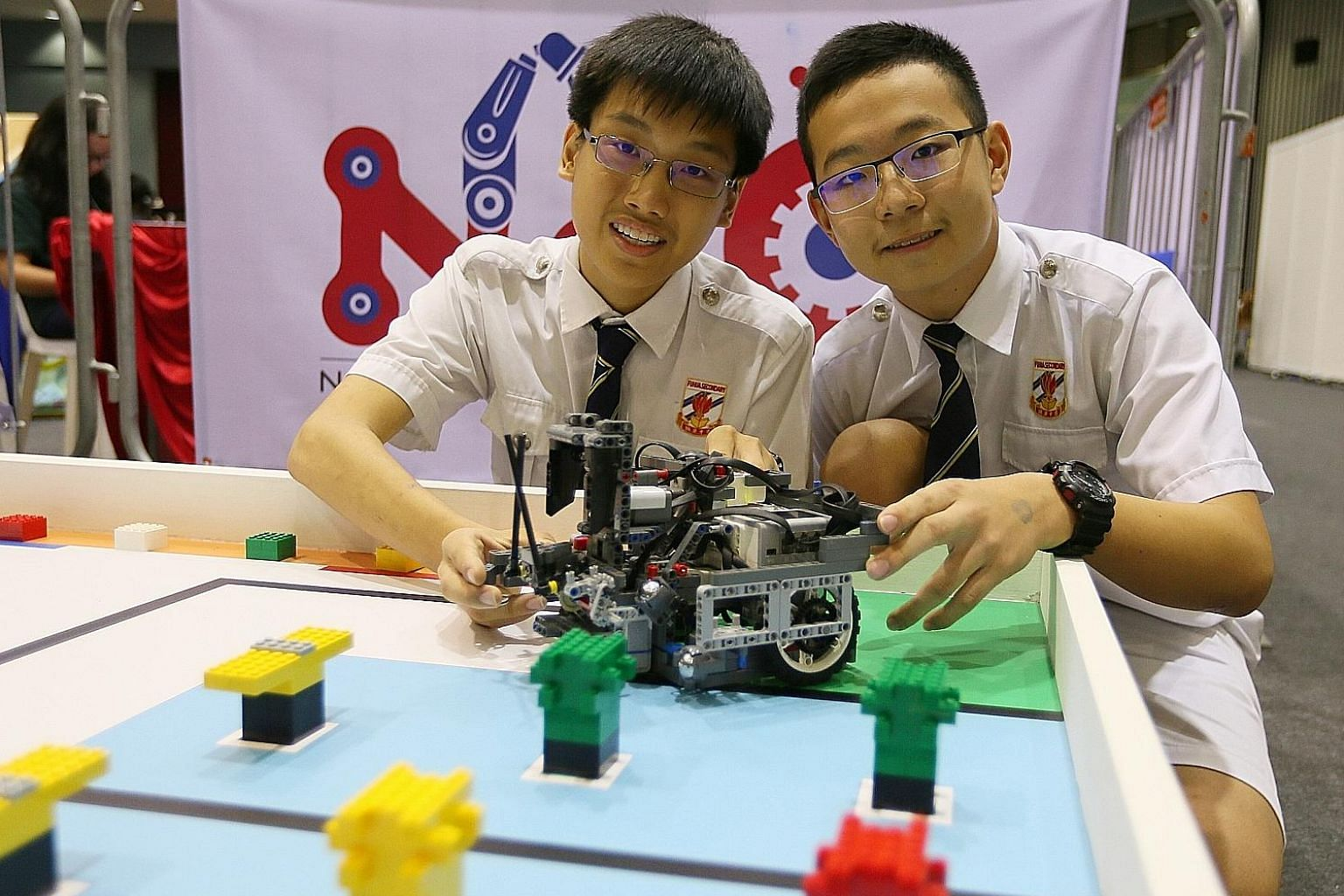 Dong Ruidi (far right) and Ng Chee Fong spent about 20 hours a week over the last few months to come up with their winning robot.