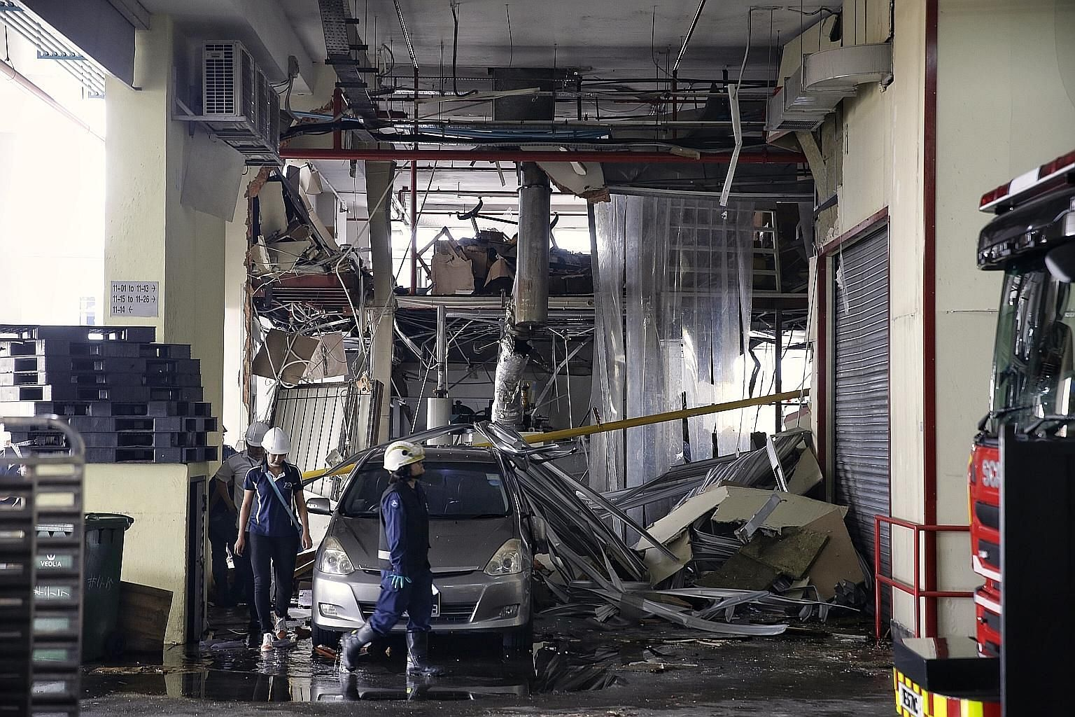 A Singapore Civil Defence Force officer and Manpower Ministry staff surveying the damage caused by an explosion at an 11th-floor unit at Enterprise Centre in Bukit Batok Crescent. Windows were shattered and frames left dangling after the blast, but t