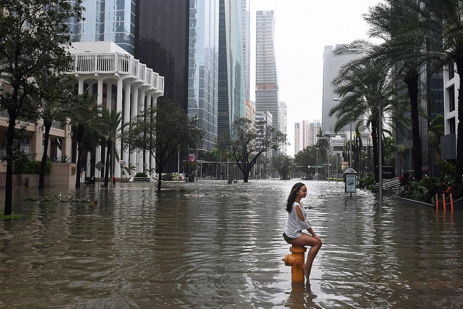 A Miami resident keeping her cool as the street turns into a river around her on Sunday. Irma's force might be diminished, but its potential for flash floods and staggering rainfall was not. Government forecasters said up to 38cm of rain was possible