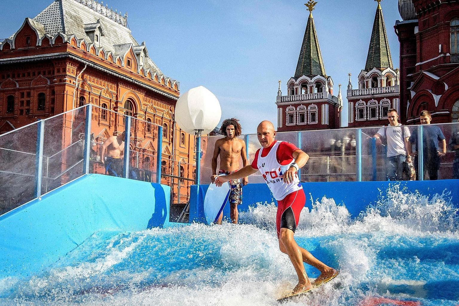 A man riding a flowboard on an artificial wave structure installed next to the Red Square and the Kremlin in Moscow on Tuesday. Various attractions were installed throughout the city to mark the 870th anniversary of Moscow.