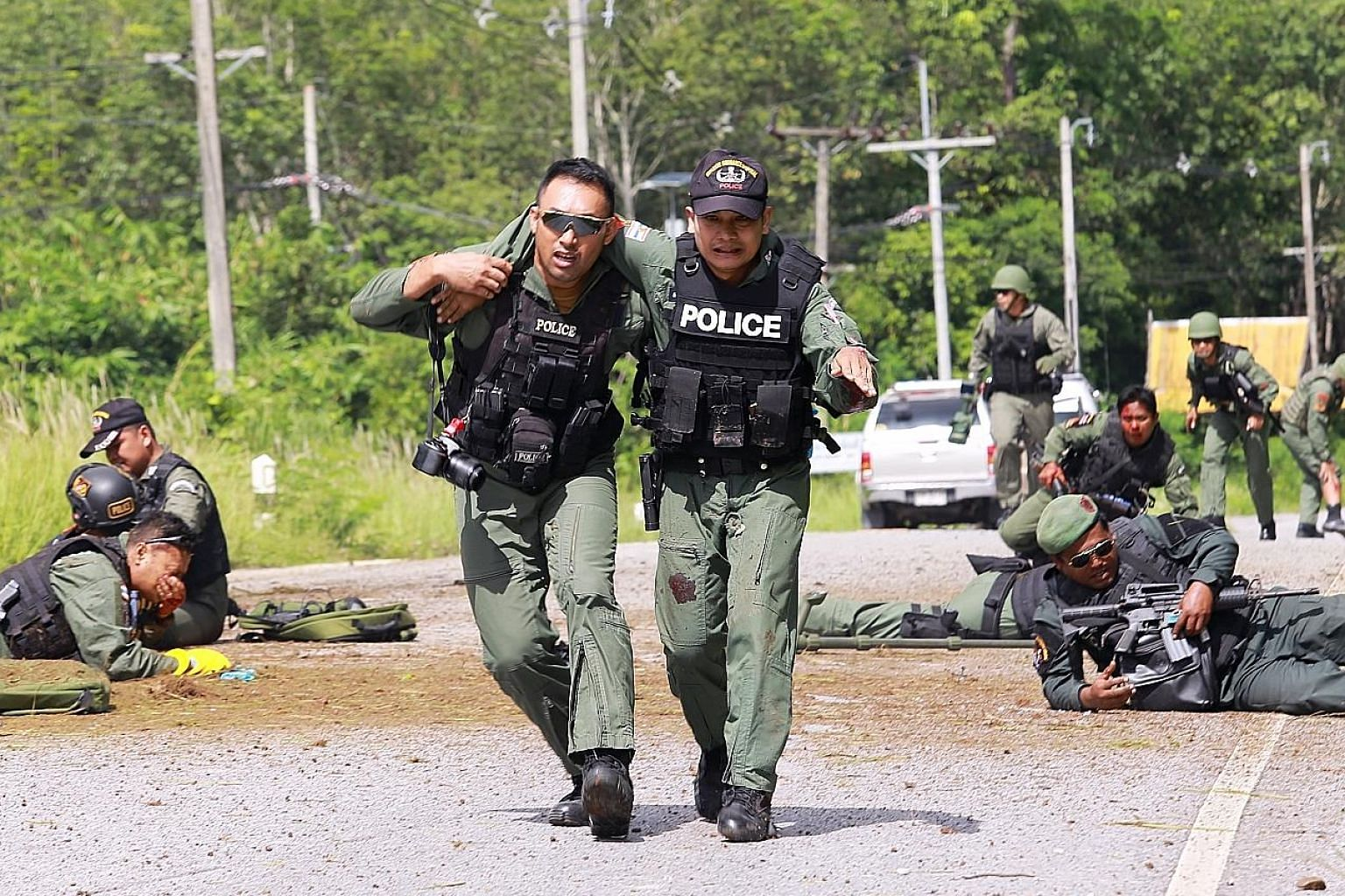 Police officers and bomb squad personnel helping injured comrades after a roadside attack in Yala province, southern Thailand, yesterday.