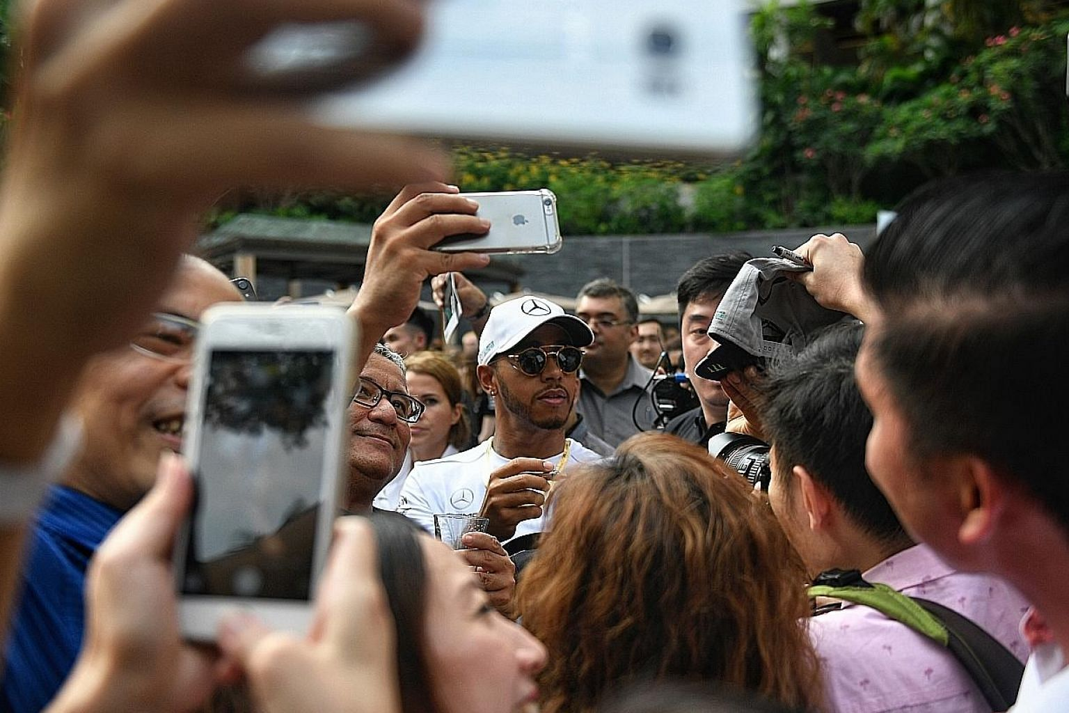 Mercedes driver Lewis Hamilton (centre) is mobbed by fans at a private meet-and-greet session at The Ritz-Carlton Millenia yesterday.