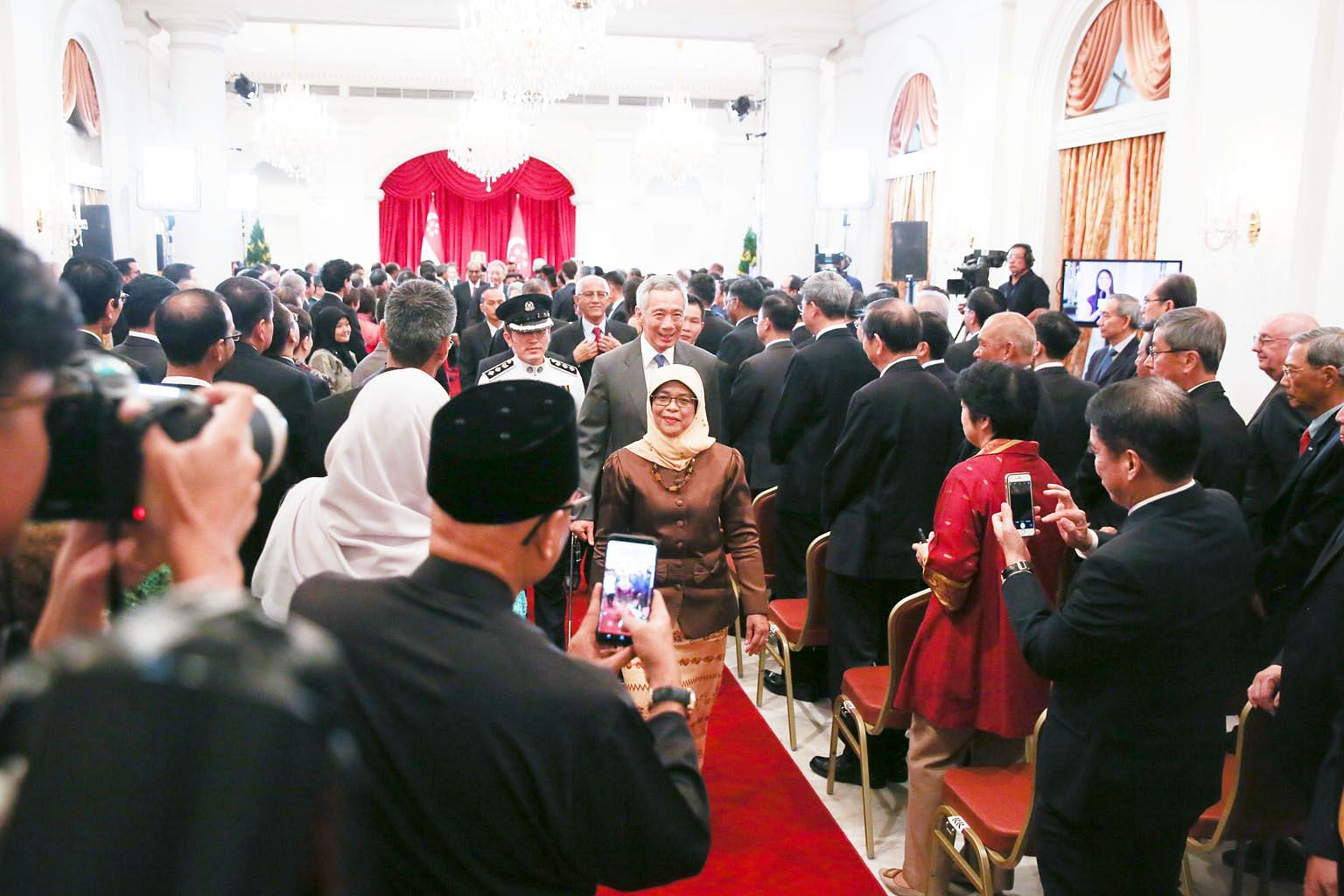 President Halimah Yacob leaving the State Room in the Istana after being sworn in yesterday. With her are Prime Minister Lee Hsien Loong and her husband, Mr Mohamed Abdullah Alhabshee (in red tie, behind PM Lee).