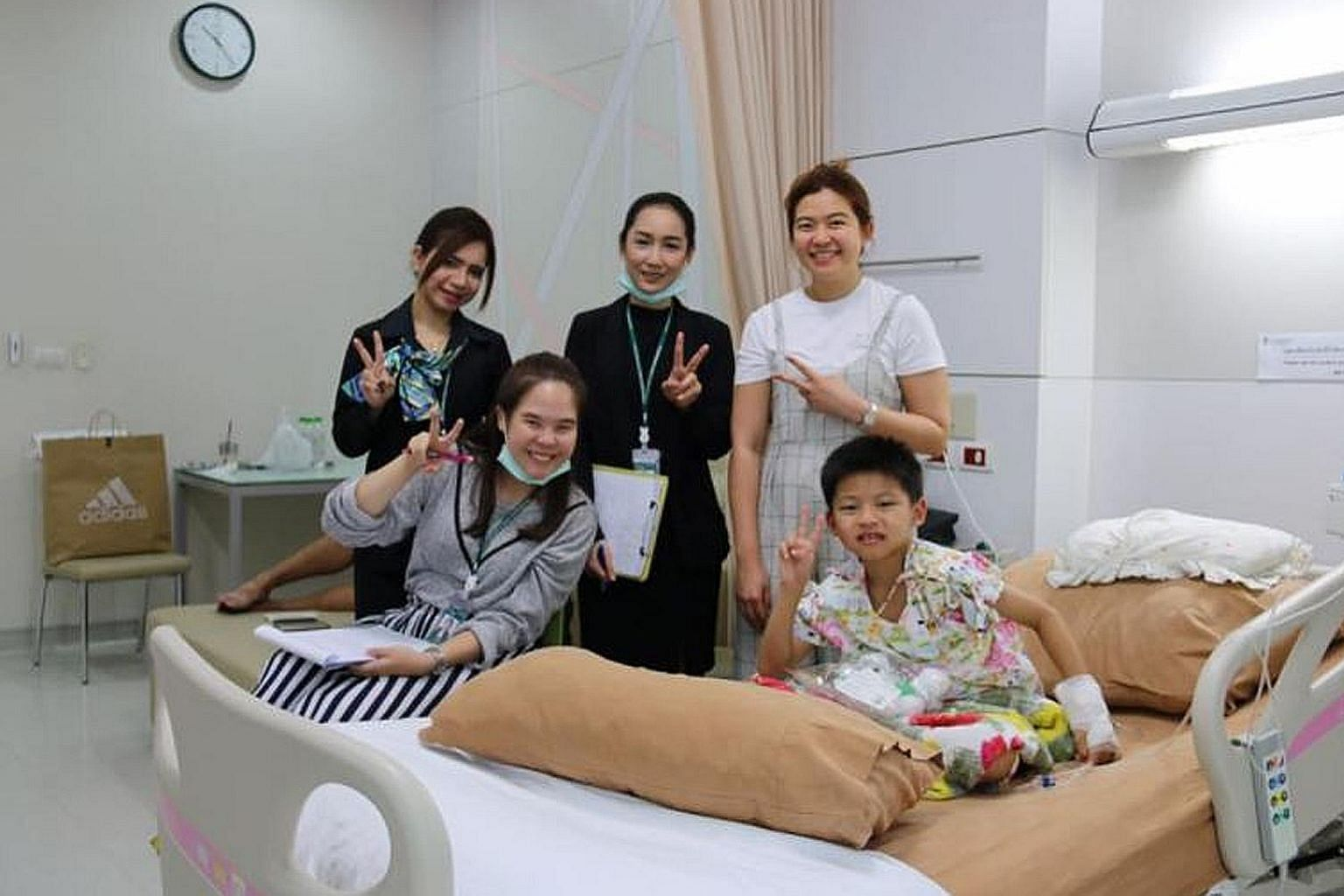 """Ms Nitcharee """"Nong Than"""" Peneakchanasak, together with hospital staff, giving moral support to a young patient in the wards."""