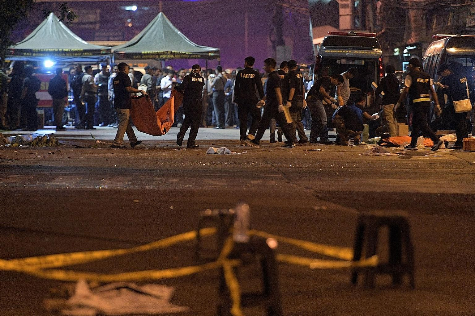 Police investigators at a bus station in Kampung Melayu, East Jakarta, on May 25, where two suicide bombers killed three policemen and injured more than 10 people.