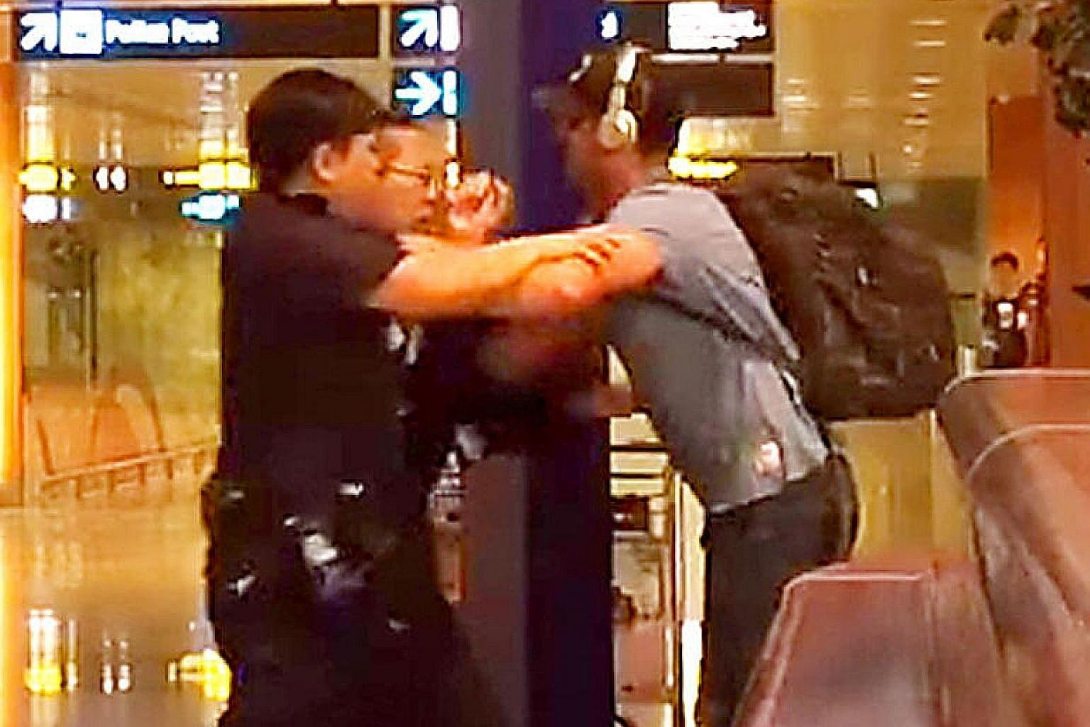 Screen grab from a video showing Jason Peter Darragh tussling with police officers at Changi Airport in April.