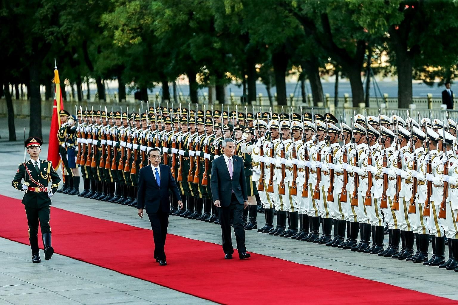 Prime Minister Lee Hsien Loong and Chinese Premier Li Keqiang inspecting the guard of honour at a welcome ceremony in front of the Great Hall of the People before their meeting in Beijing yesterday.
