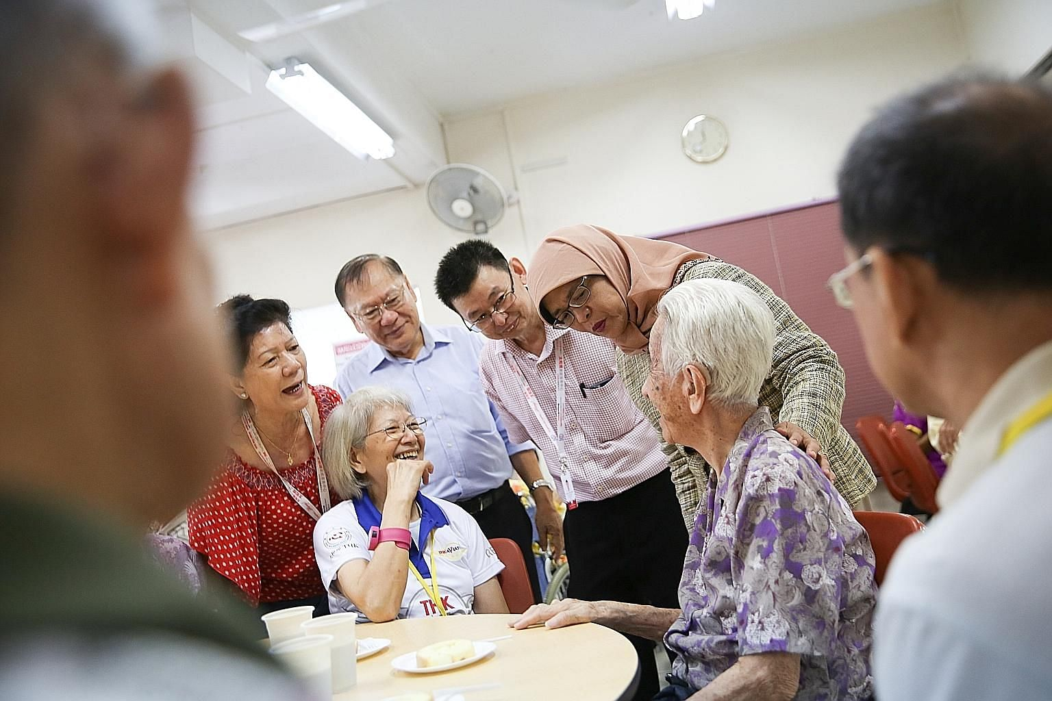 President Halimah Yacob, with THK Moral Charities chairman Lee Kim Siang (in light blue shirt), on a visit to the THK Indus Moral Care seniors activity centre in Tiong Bahru yesterday. The charity offers a drop-in disability programme at four of its