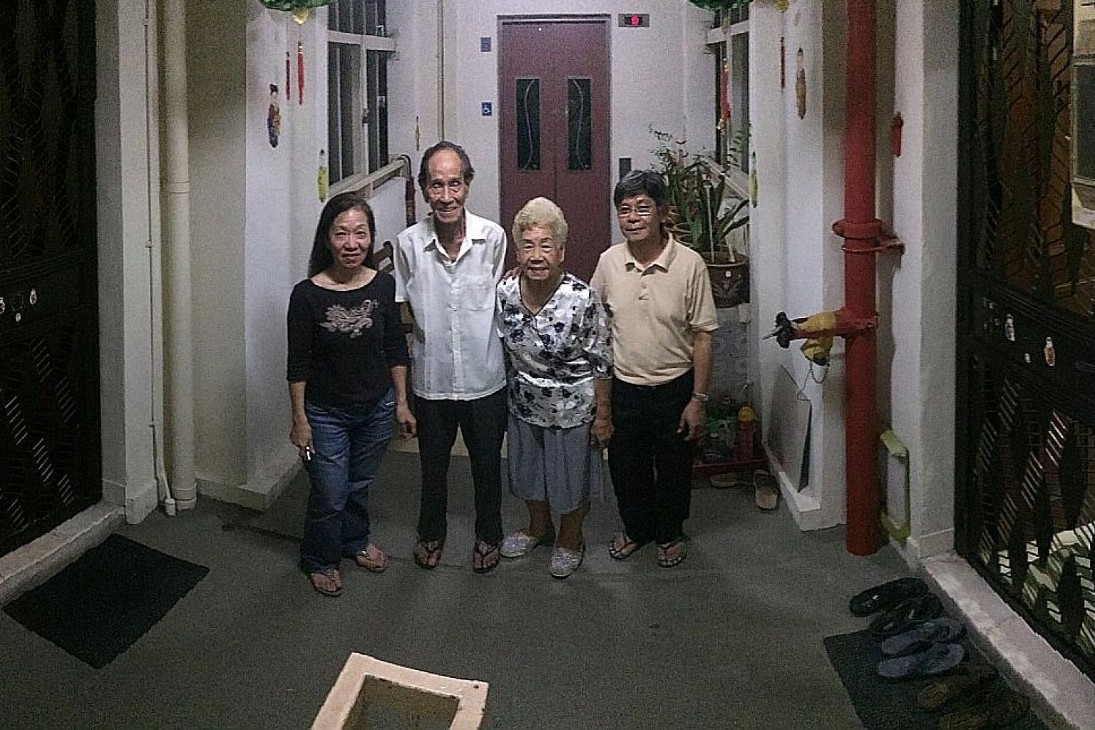 Madam Lucy Tan (far left), with her parents-in-law, Mr Koh Woo Keng, 87, and Madam Chan Mui Gek, 84, and her brother-in-law, Mr Willy Koh, 60, at the lift lobby in between the front doors of their jumbo flat.