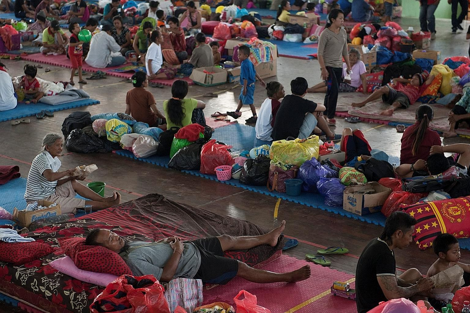 Balinese taking refuge at a temporary evacuation centre yesterday as Mount Agung continued to send out signals of imminent eruption. More than 120,000 people have fled to safety, and officials have warned people to stay at least 9km away from the vol
