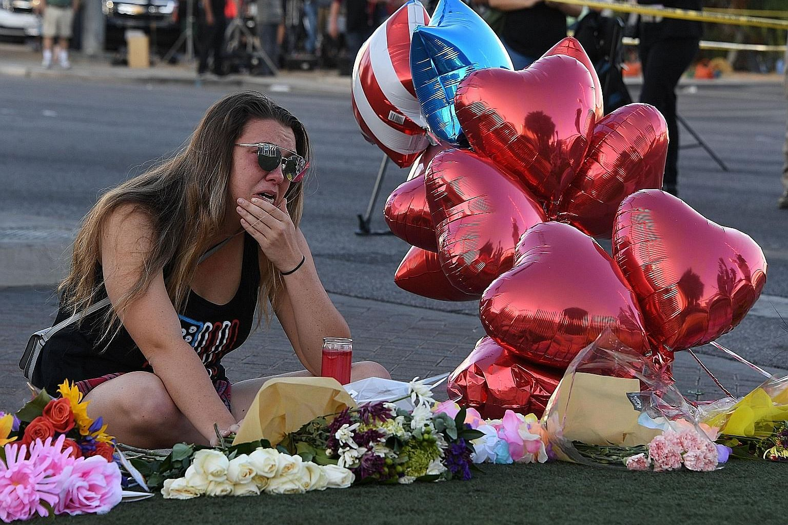 Ms Destiny Alvers, who attended the Route 91 country music festival and helped rescue her friend who was shot, grieving as she sat at a makeshift memorial on the Las Vegas Strip on Tuesday. Investigators are at a loss as to Stephen Paddock's motive f