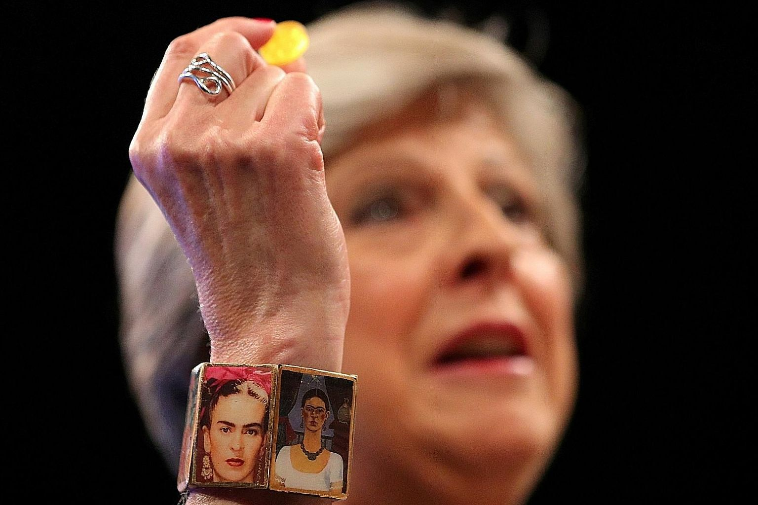 British PM Theresa May, with a bracelet bearing images of Mexican artist Frida Kahlo, holding a sweet passed to her after she was seized by a coughing fit as she addressed her party in Manchester on Wednesday.