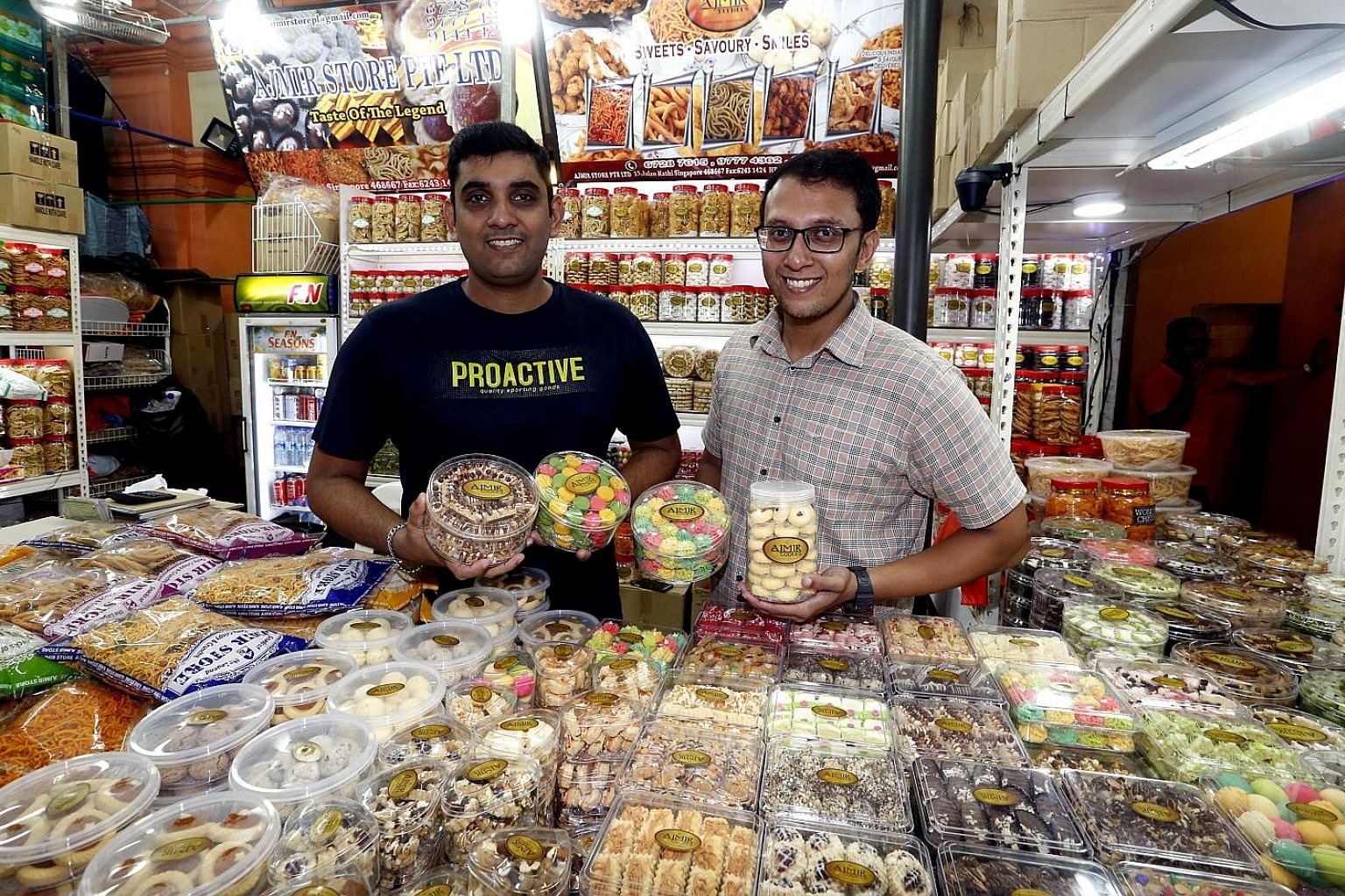Brothers Mohamed Faizal (left) and Mohamed Ismail, who run Ajmir Store in the Deepavali Festival Village, with their new snacks.
