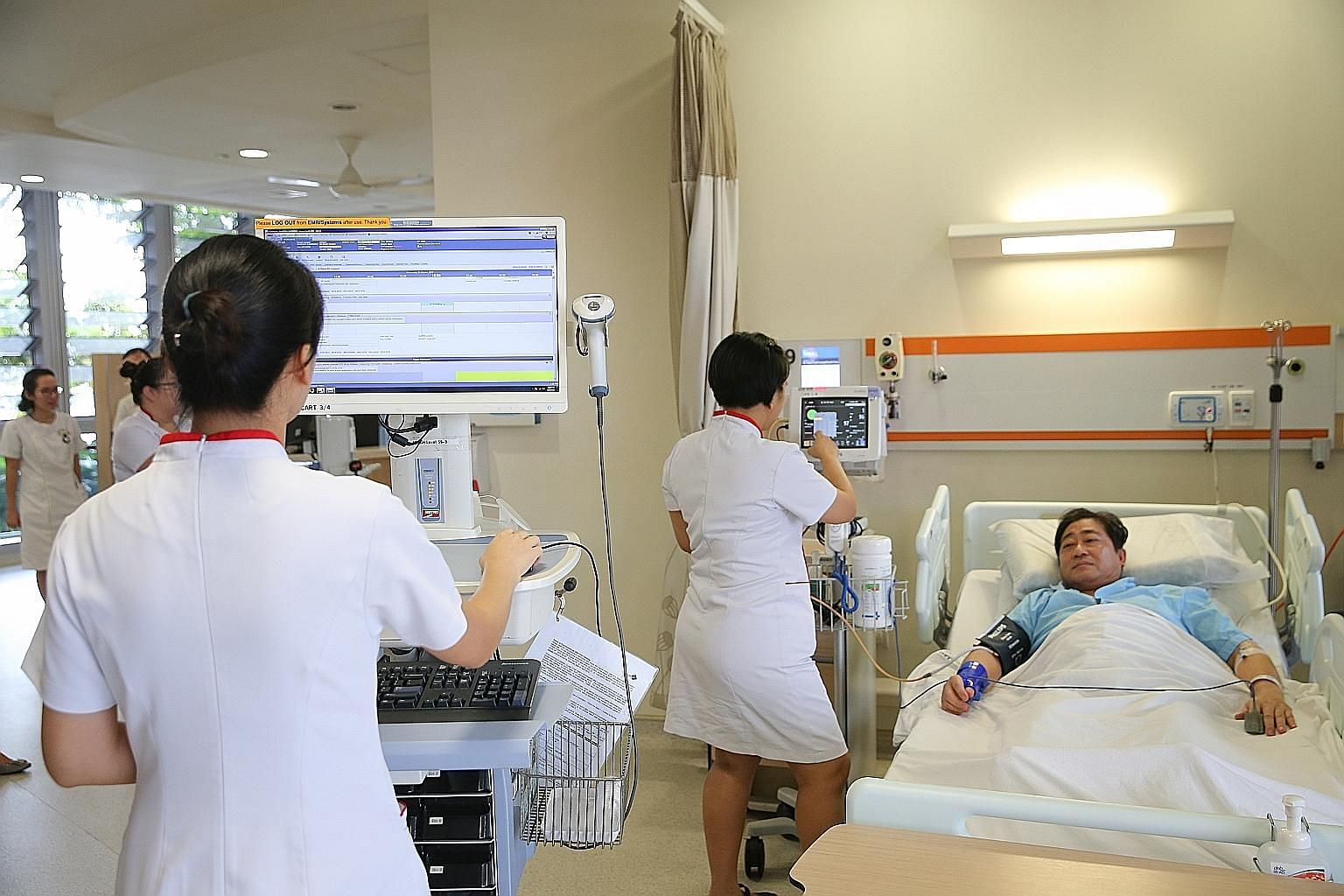 """A nurse uses the """"Computer on Wheels"""" with a medication cart. It is able to access a patient's records and track his vital signs. Vital signs readings are transmitted wirelessly and captured. This process was traditionally done using pen and paper."""