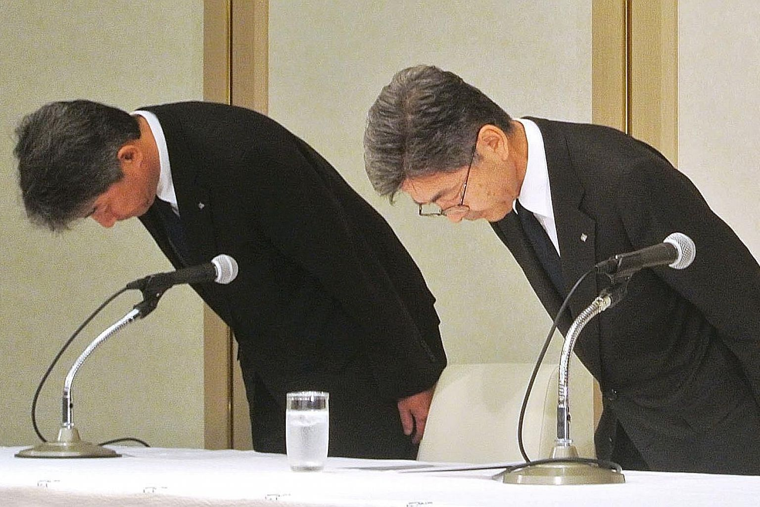Kobe Steel's executive vice-president Naoto Umehara (right) apologising at a news conference in Tokyo on Sunday. Shares of the company plunged 22 per cent.
